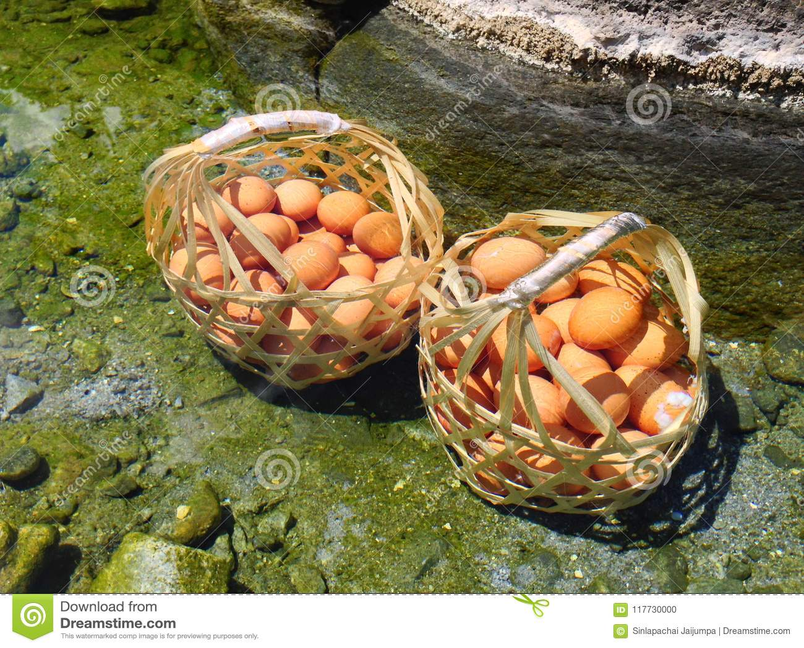Много яичек цыпленка в деревянной корзине кипеть на горячем источнике