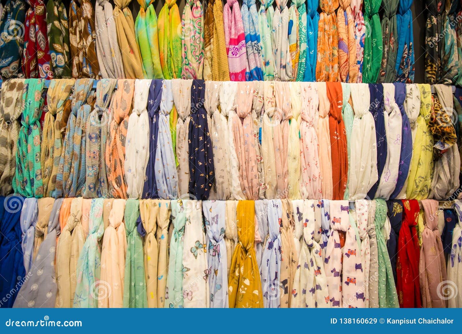 Много ярких женских шарфов и шаль Красочные шарфы вися в рынке Одежды кладут на полку с выбором шарфов или шарфов