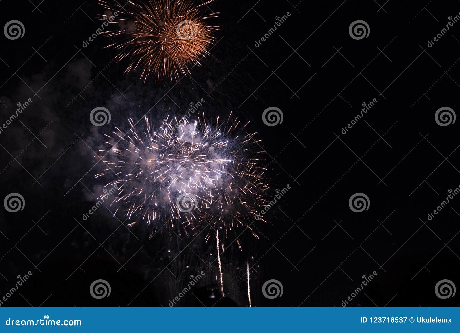 Множественные фейерверки в ночном небе в составе в тенях красных и белых