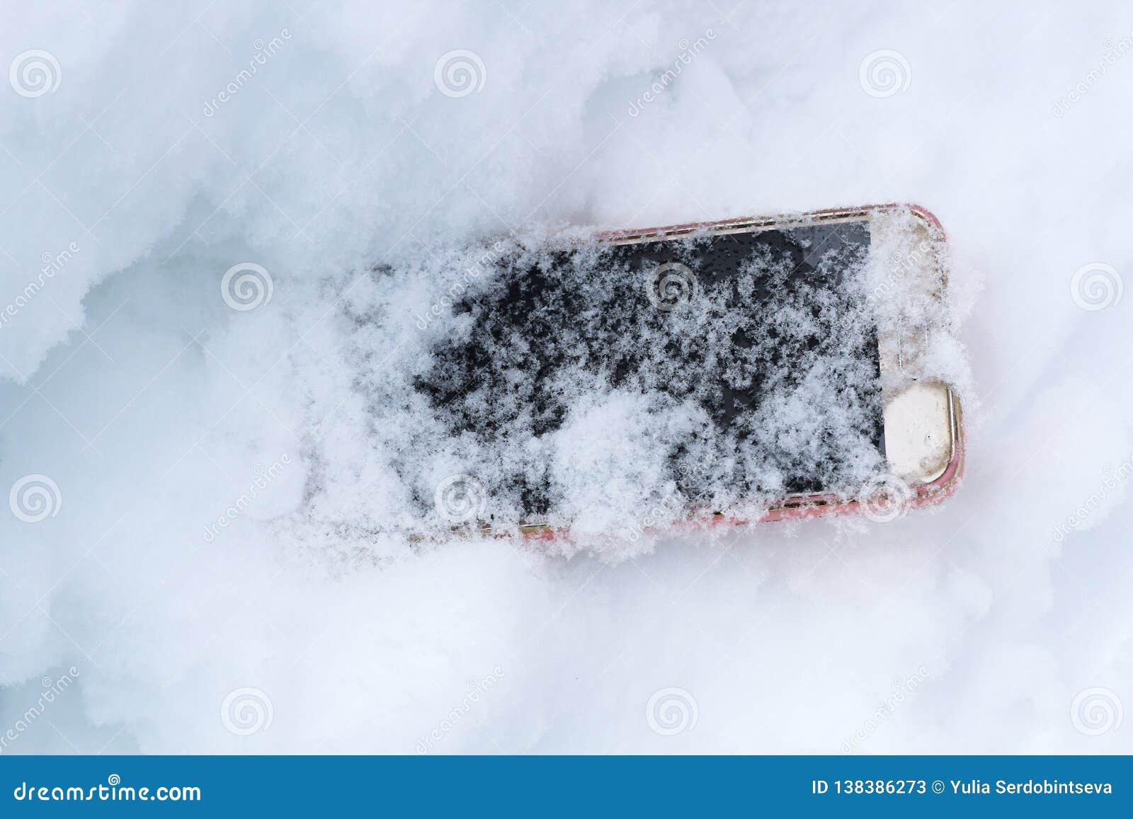 Мобильный телефон случайно упал вне и выпаданный из ускорения в снеге