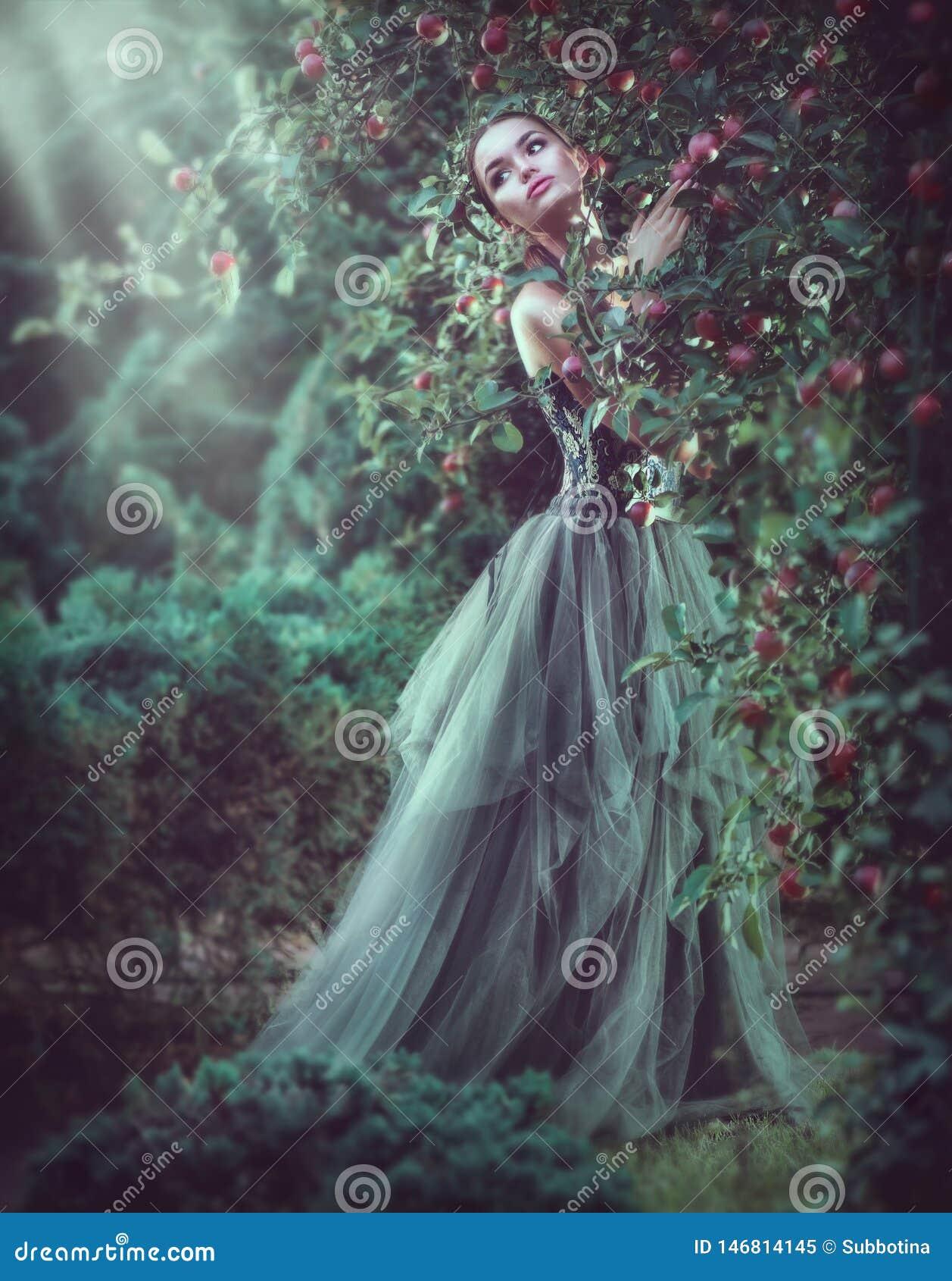 Мода девушки красоты романтичная модельная представляя в деревьях сада, наслаждаясь природой в яблоневом саде Woma красивого брюн