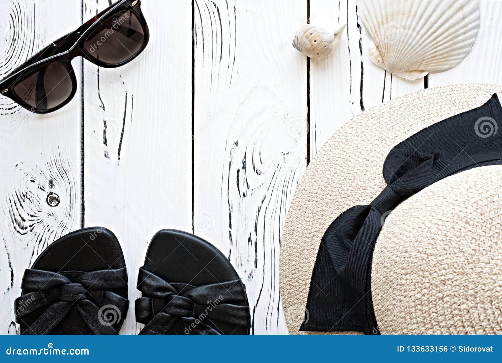 Мода лета flatlay с солнечными очками, раковинами моря, песком женщин