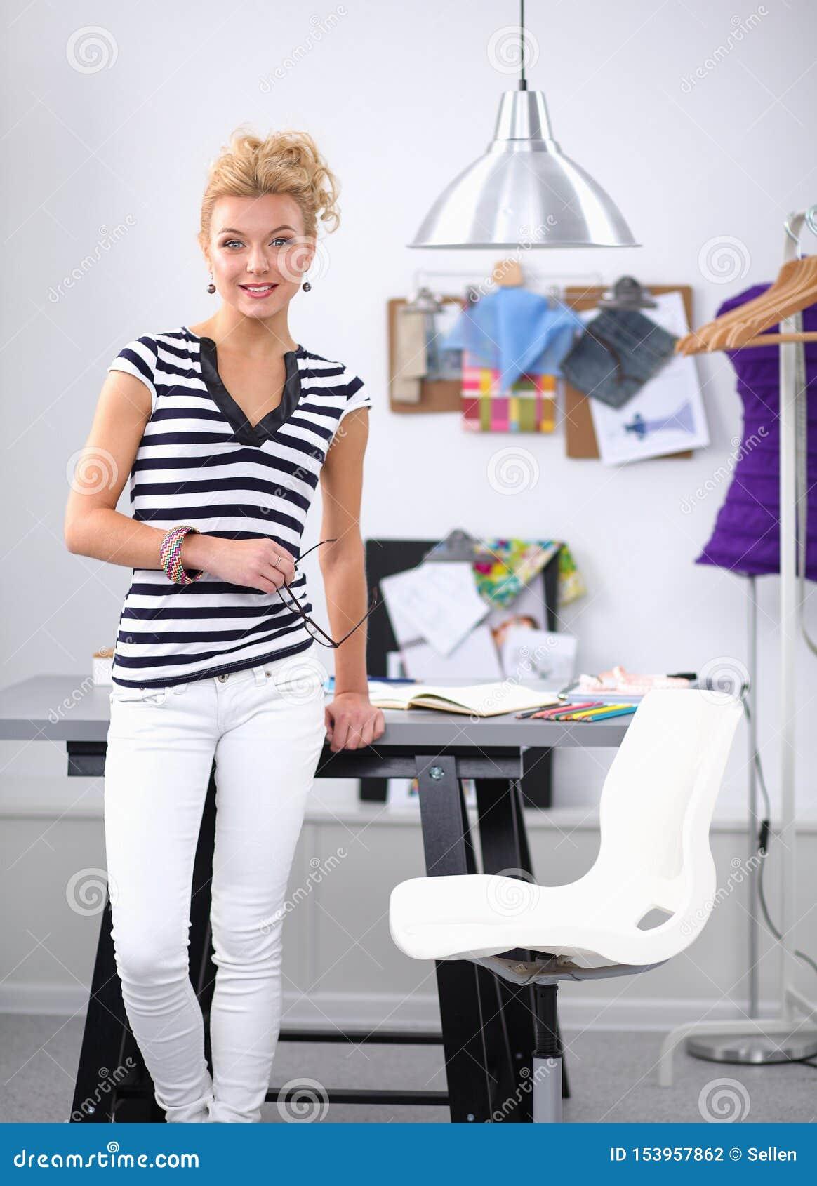 Модельер работая на ее дизайнах в студии