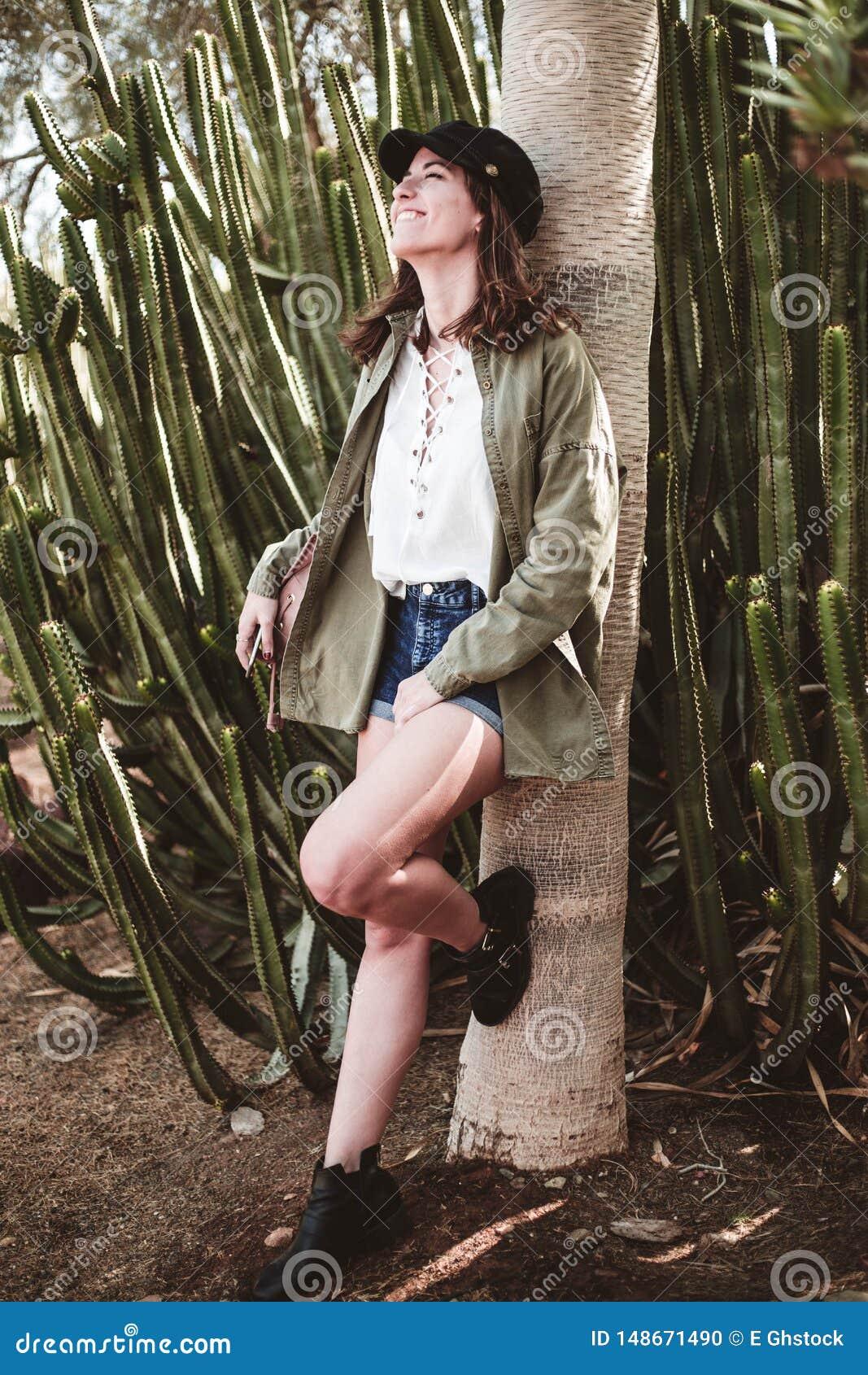 Модельный смеяться с черной крышкой отдыхая на хоботе дерева около кактуса