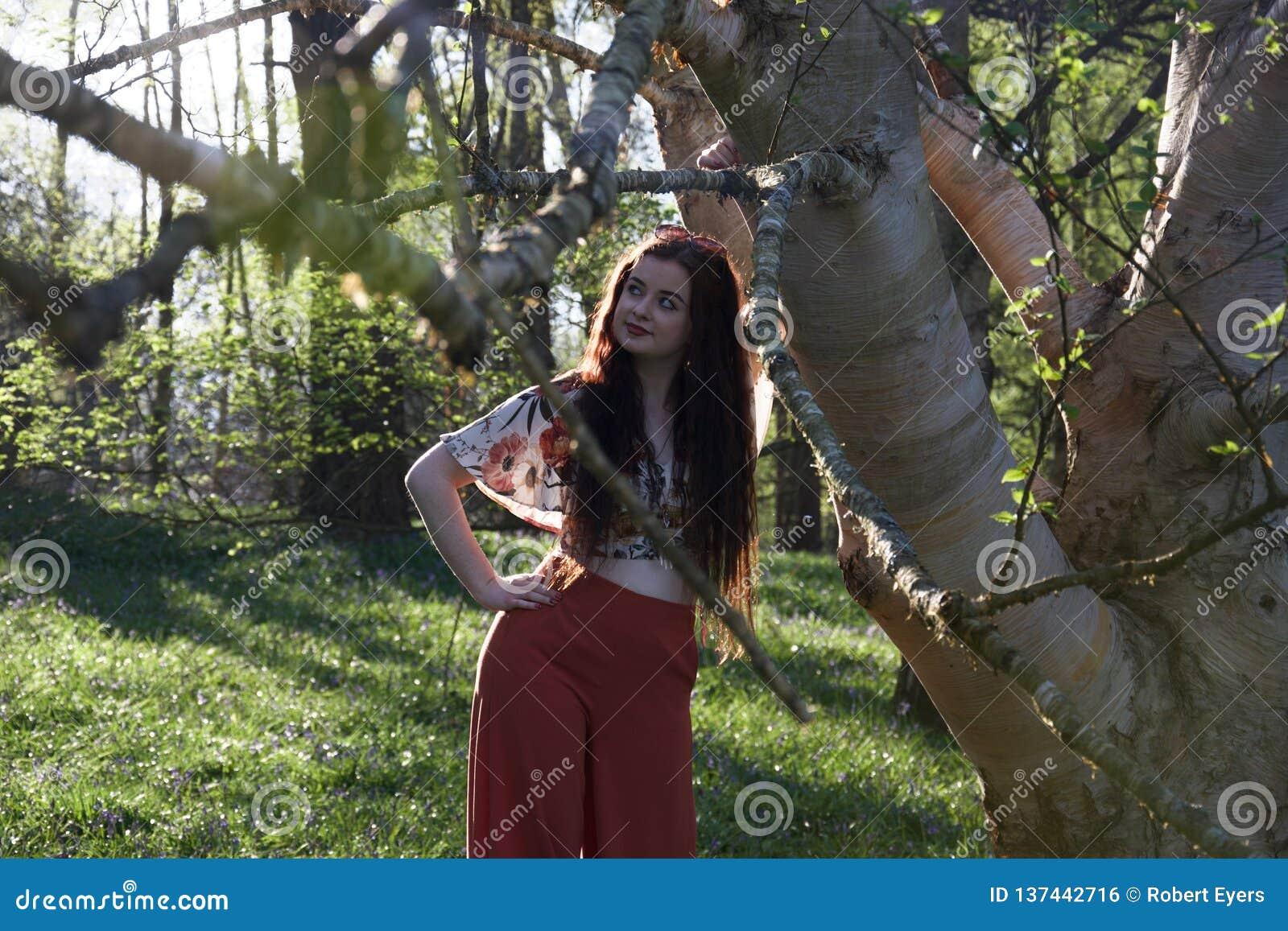 Модно одетая дама представляя с деревом серебряной березы