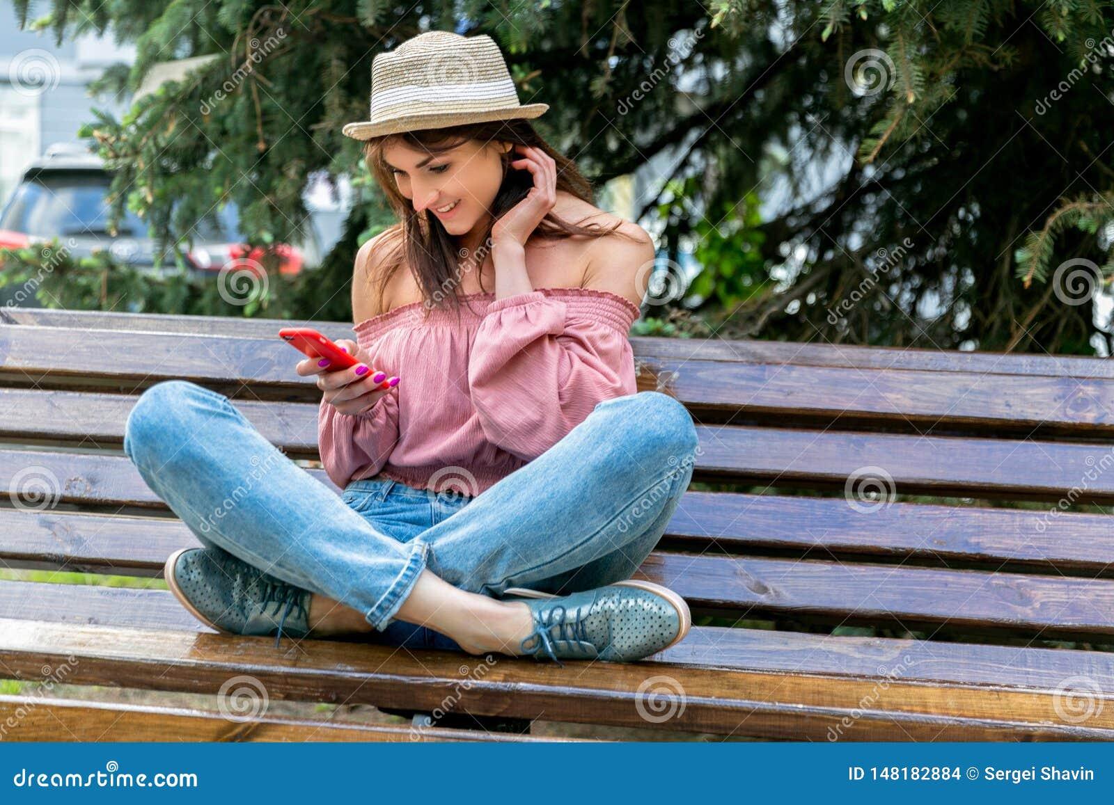 Модно одетая молодая женщина на улице на солнечном вечере Девушка в джинсах, блузке и небольшой шляпе сидит на стенде и