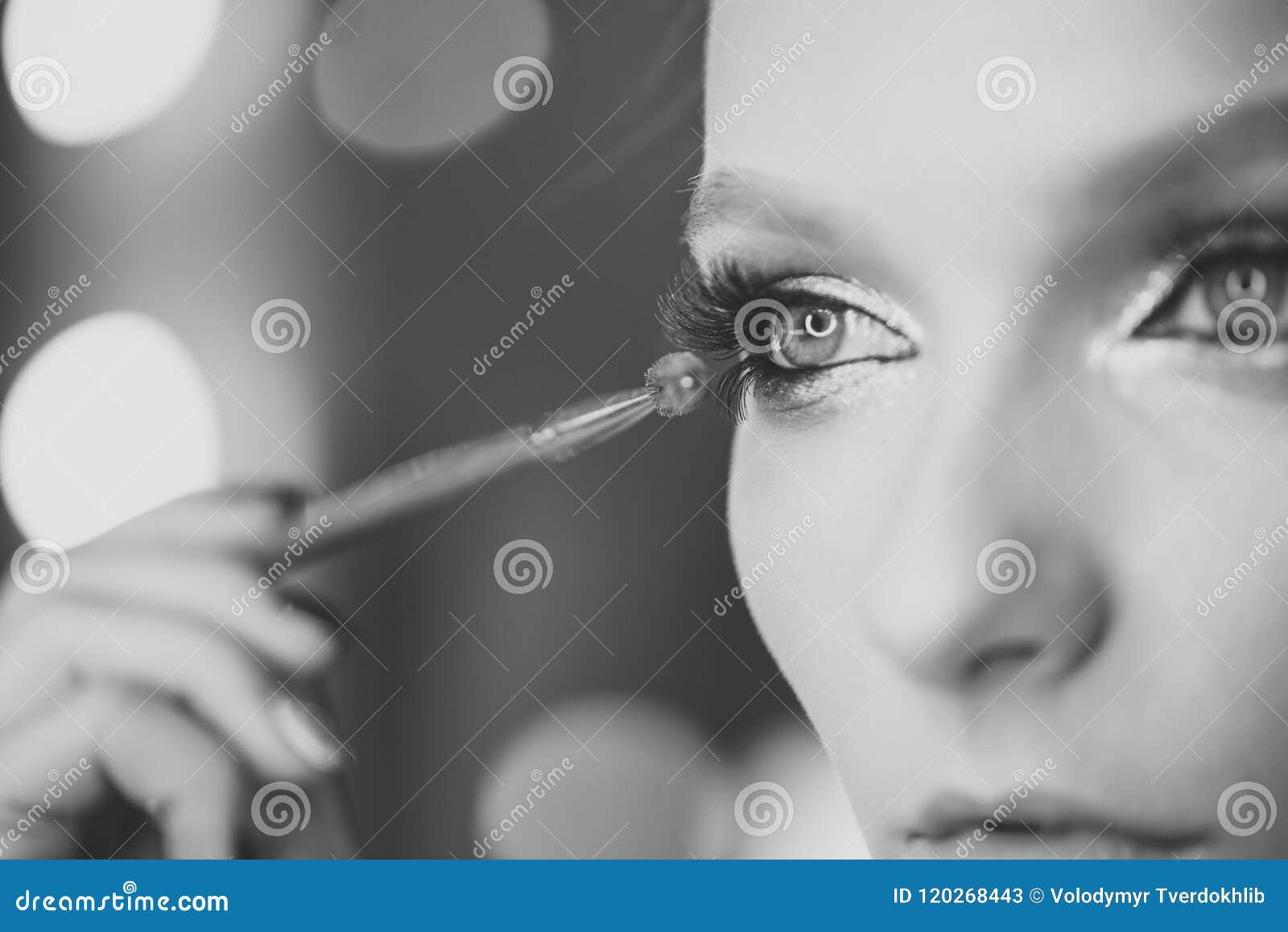 модно составьте модная представляя женщина Женщина прикладывая черную тушь на ресницах с щеткой состава Молодые