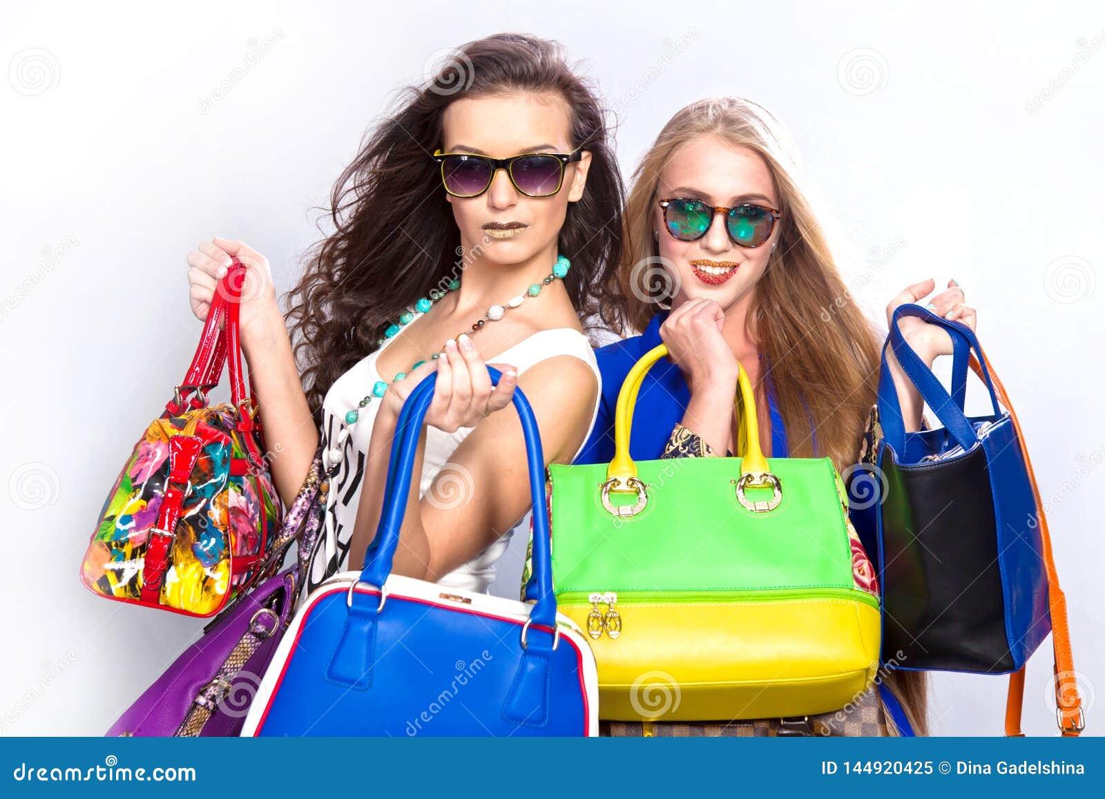 Модные красивые девушки и много кожаные сумки на серой предпосылке