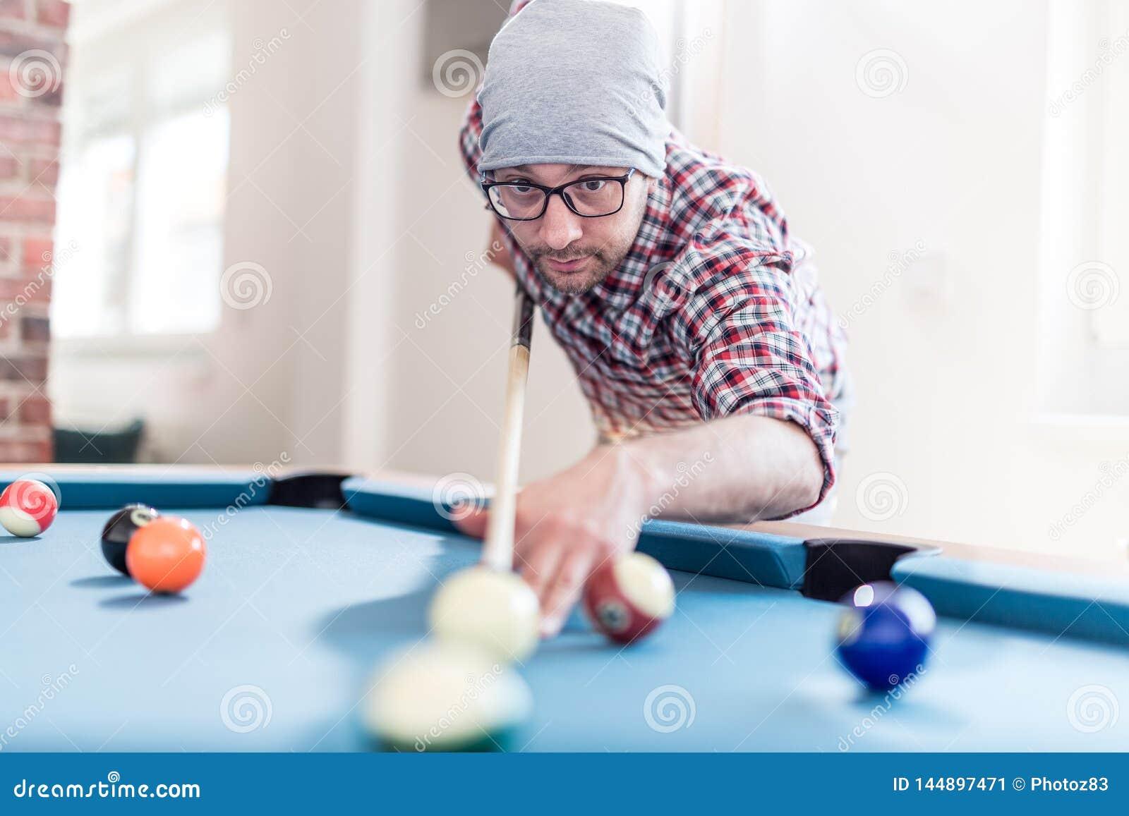 Модный городской человек играя игру билльярдов бильярдного стола