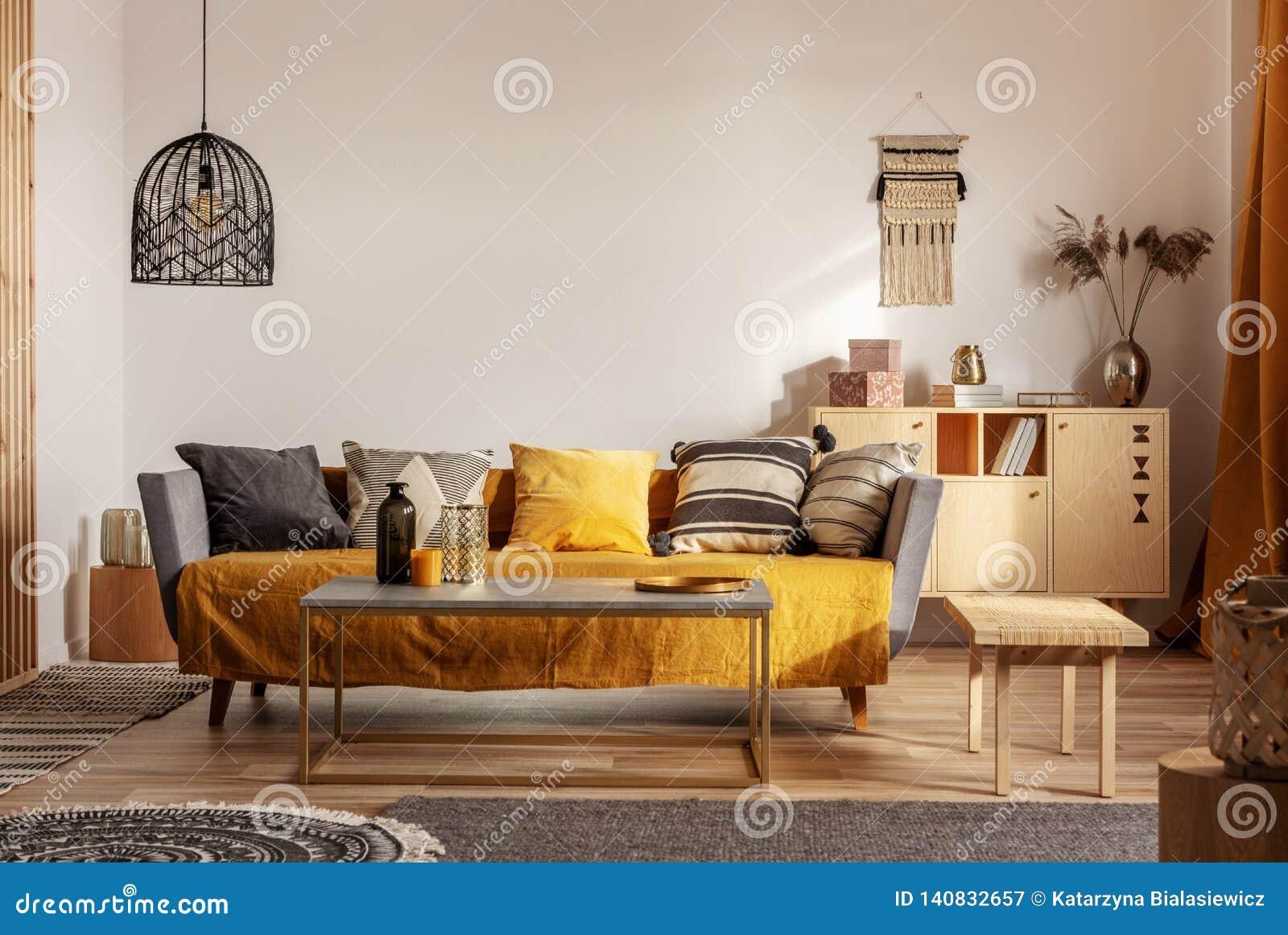 Модный интерьер живущей комнаты с желтым и серым дизайном и длинным журнальным столом в середине