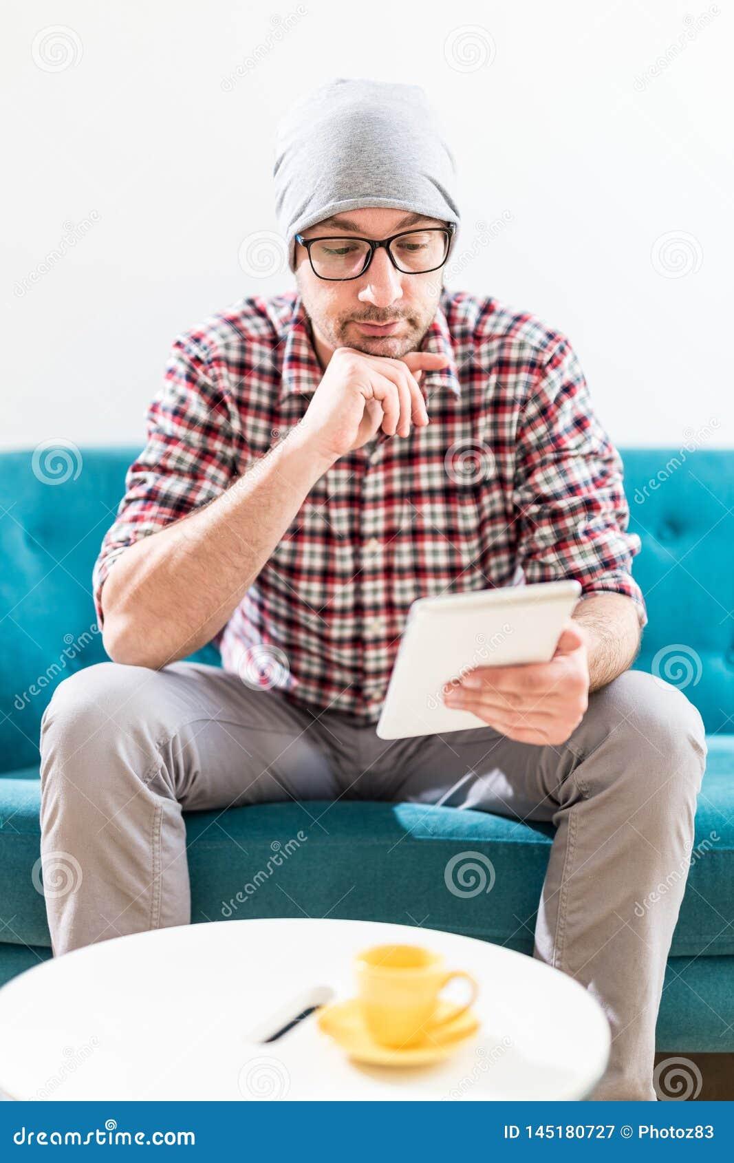 Модный молодой человек используя прибор планшета пока сидящ на его оф