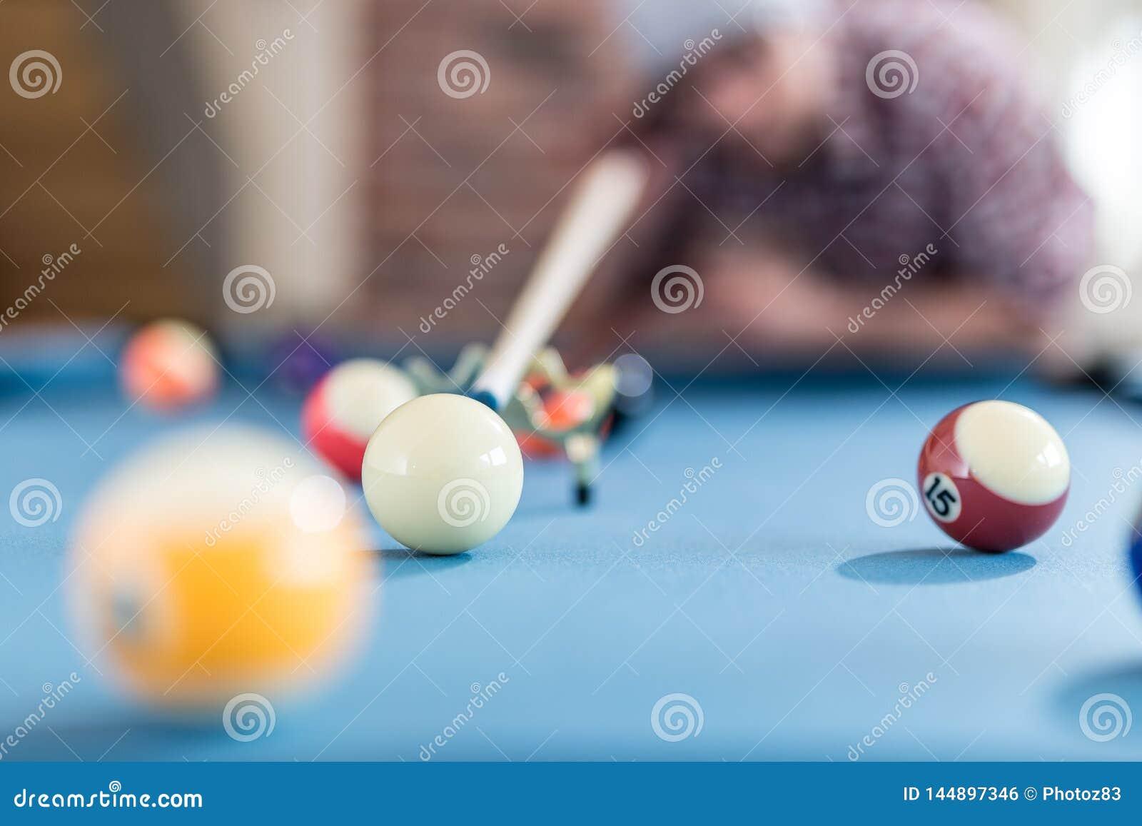 Модный человек подготавливая ударить белый шарик с сигналом снукера б