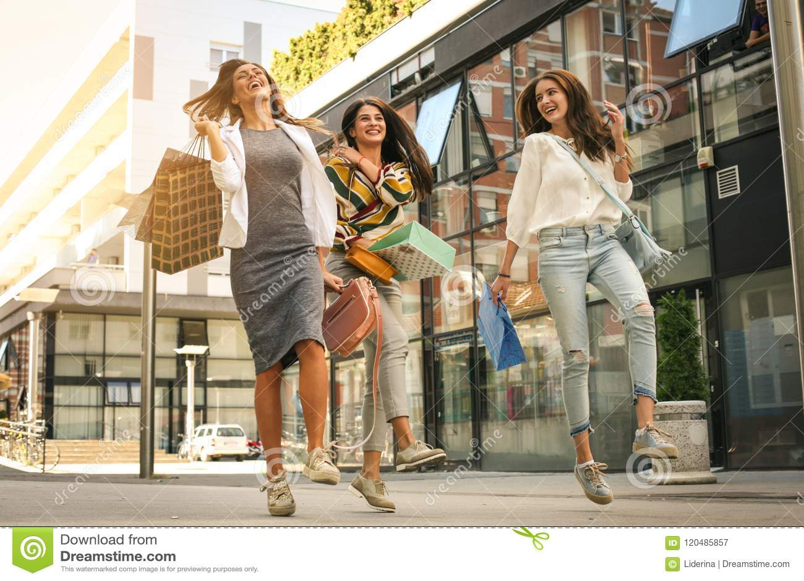 3 модных молодой женщины гуляя с хозяйственными сумками Sati