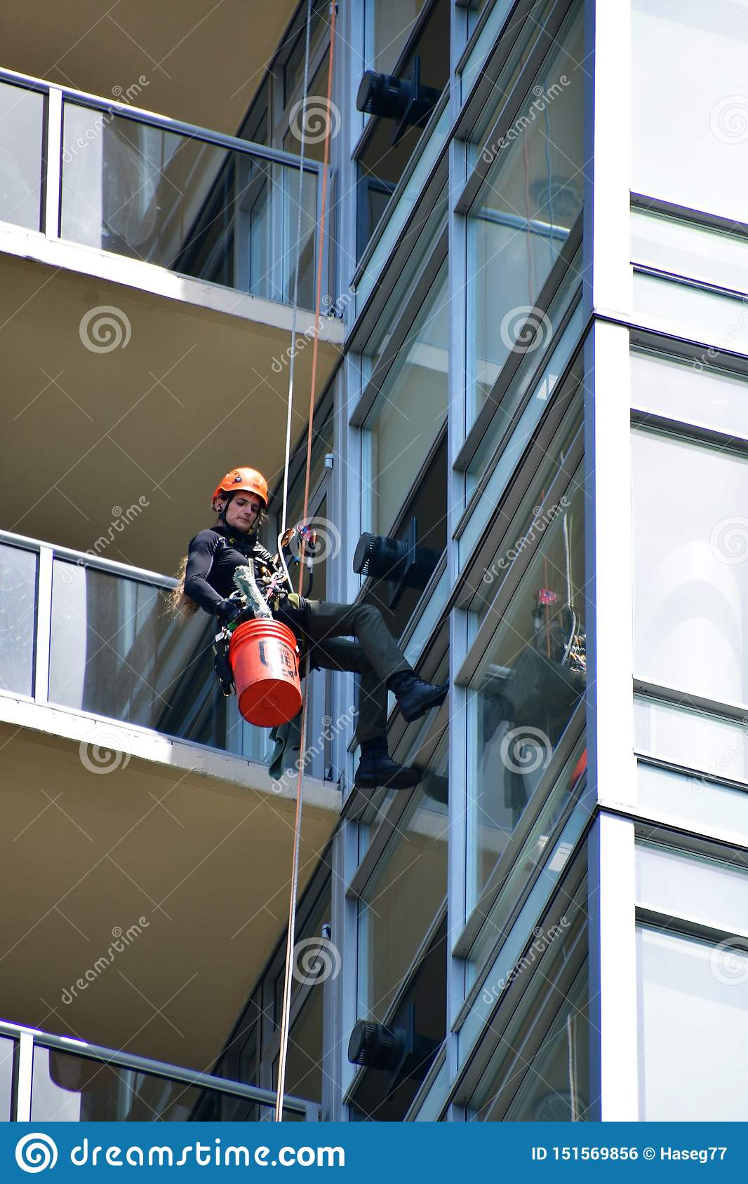 Мойщик окон очищая окно высокого здания подъема