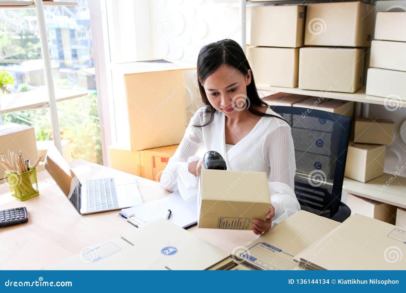 Молодая азиатская девушка начало фрилансера вверх по адресу сочинительства владельца мелкого бизнеса на картонной коробке на рабо