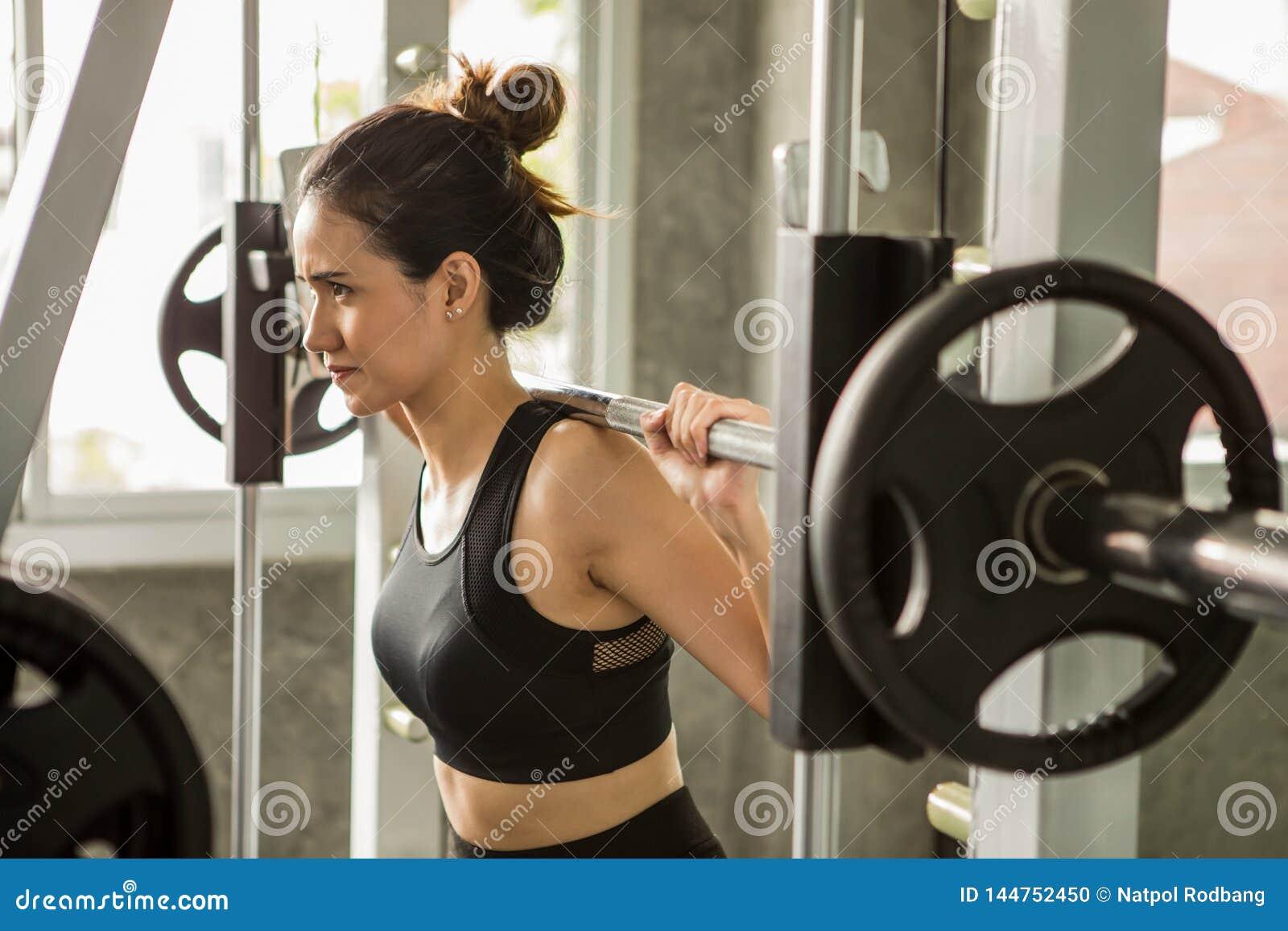 молодая азиатская женщина фитнеса в sportswear работая строя мышцы поднимая вес со штангой в спортзале разминка девушки спорта зд