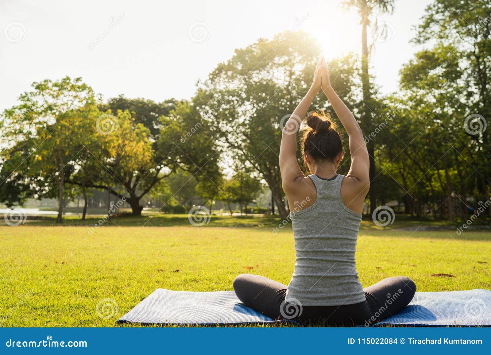 Молодая азиатская йога женщины outdoors держит затишье и размышляет пока практикующ йогу для того чтобы исследовать внутренний ми