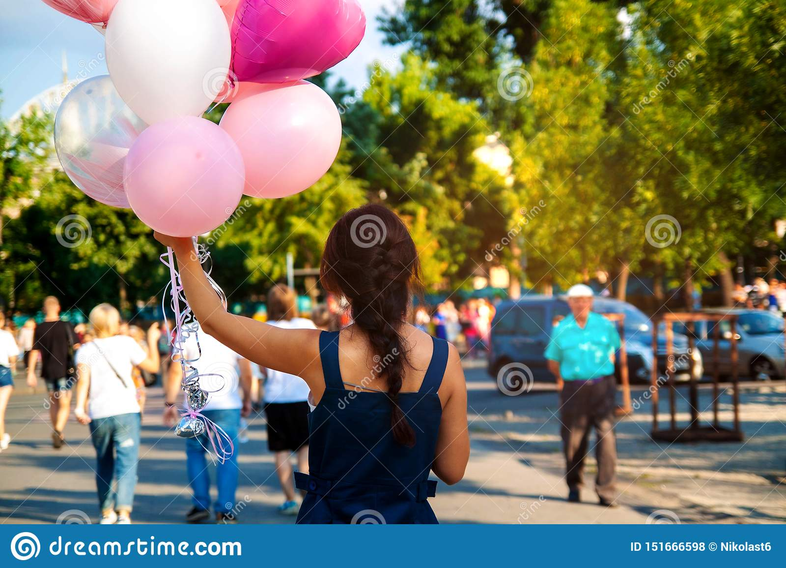 Молодая азиатская красивая женщина с воздушными шарами летания пестроткаными в городе