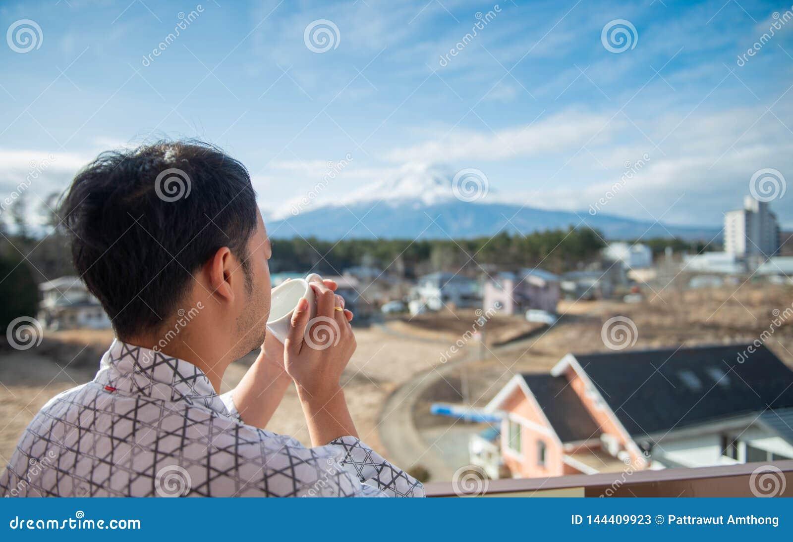 Молодая азиатская стойка человека смотря Mount Fuji
