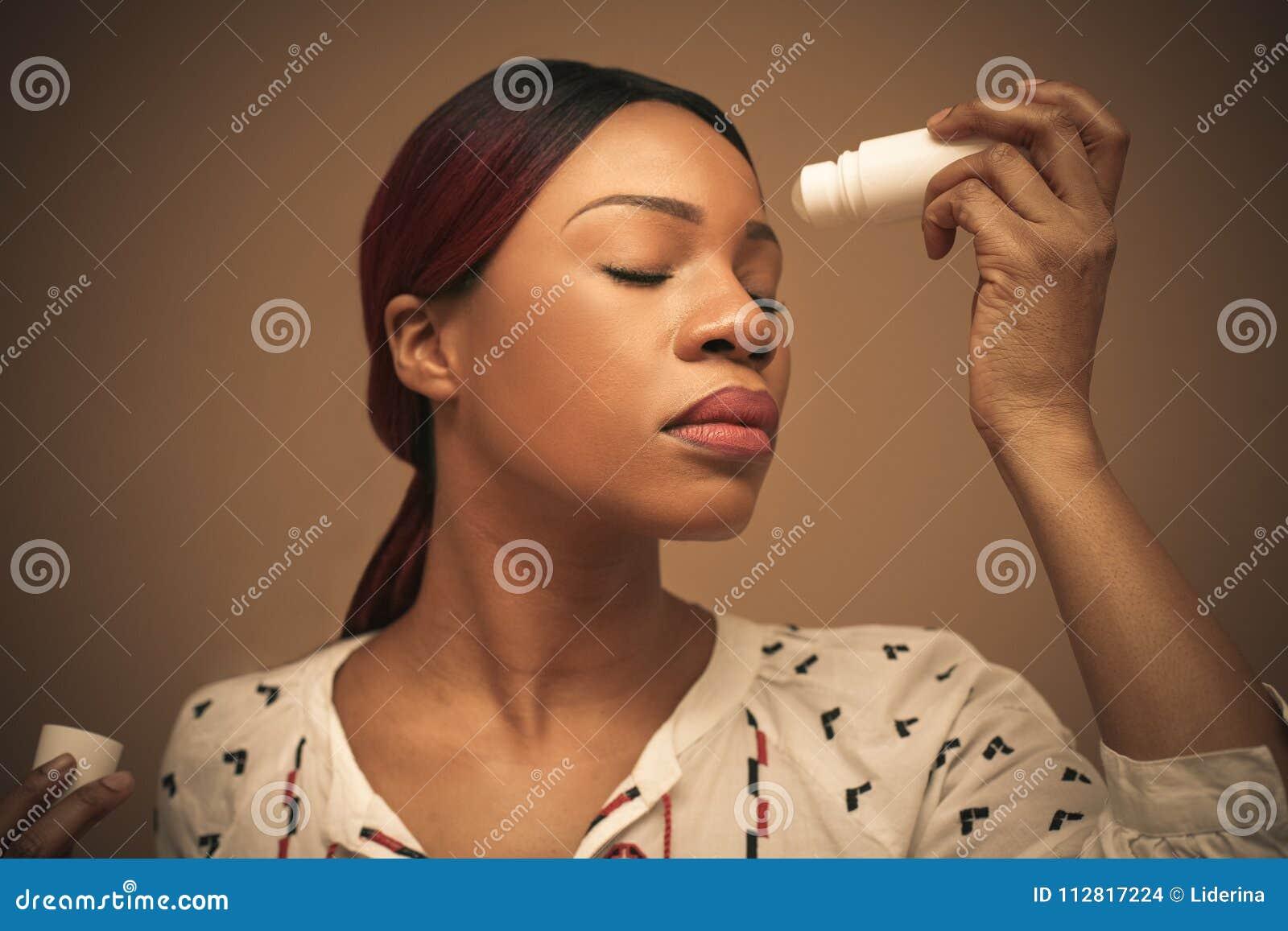 Молодая африканская женщина используя продукты красоты для ее стороны конец вверх