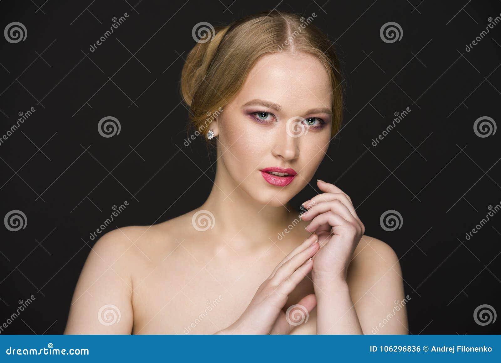 Молодая белокурая девушка при чуть-чуть плечи представляя на черноте, безшовной предпосылке в студии