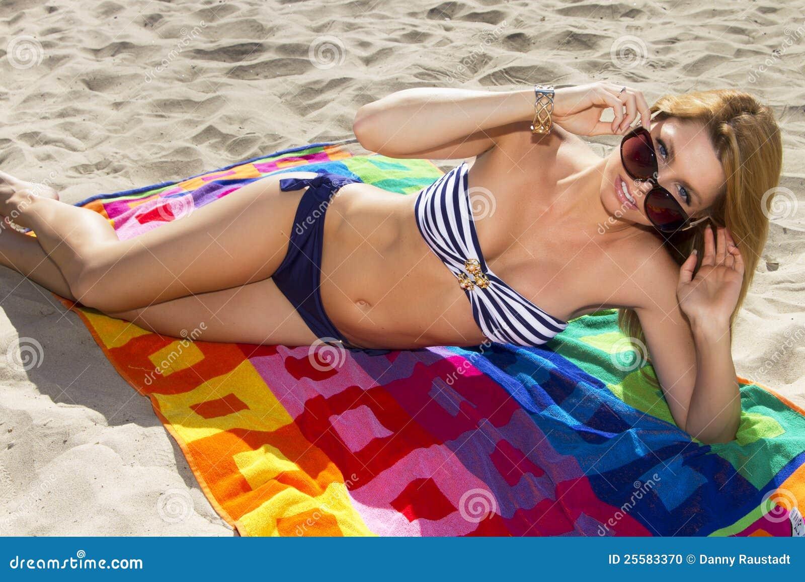 Молодая белокурая женщина отдыхая на пляже