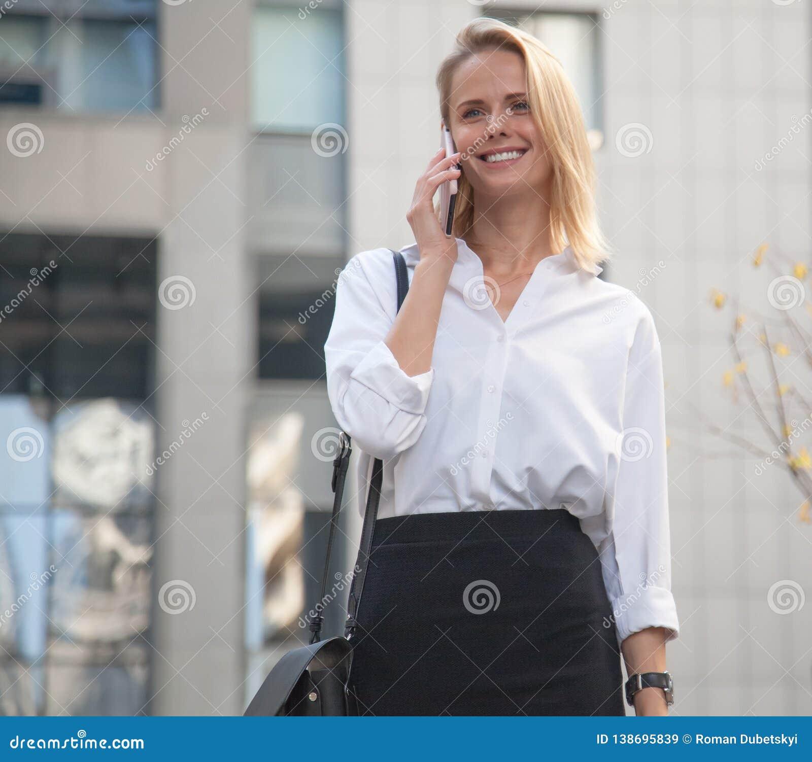 Молодая бизнес-леди перед офисным зданием используя ее сотовый телефон
