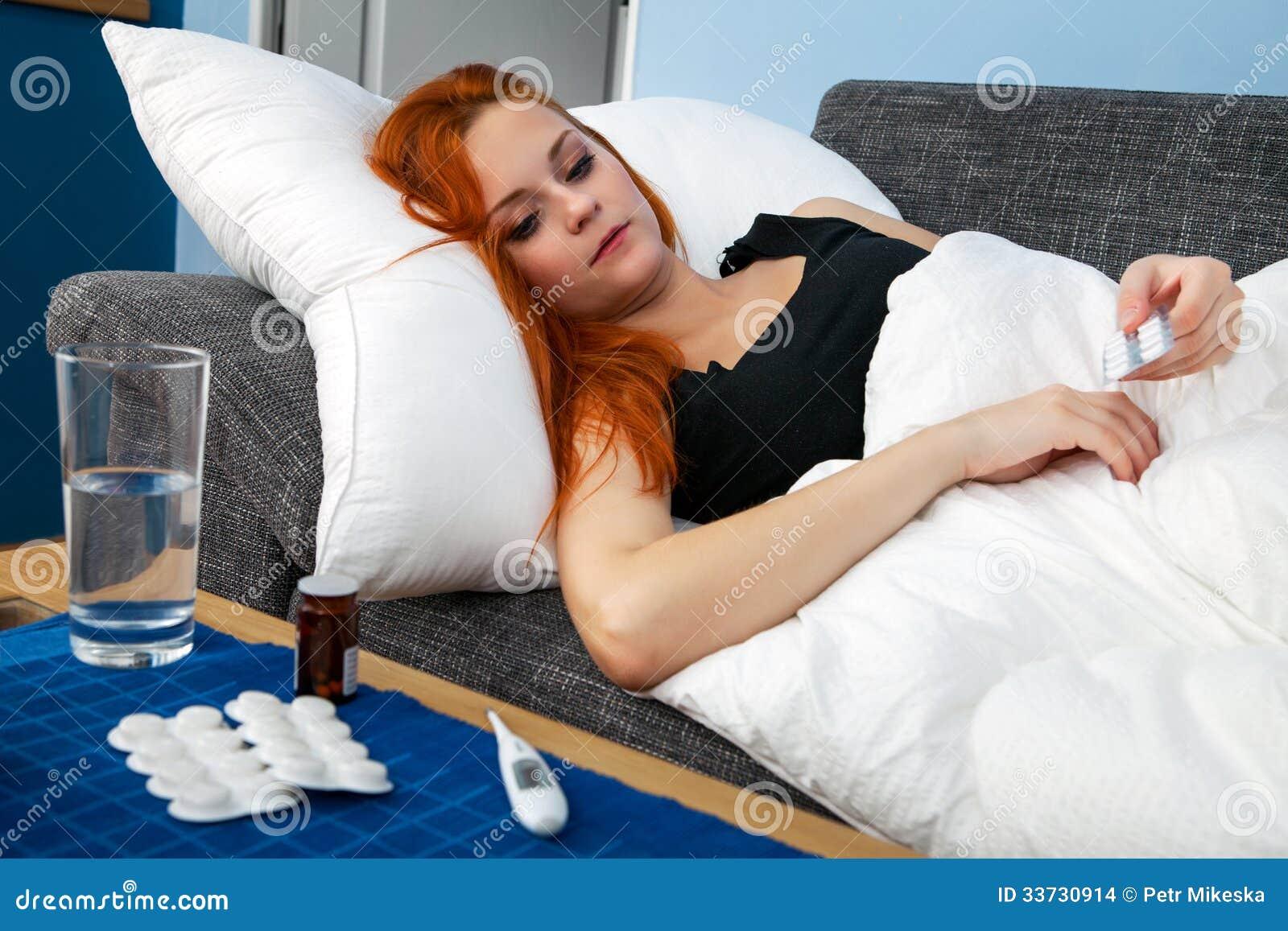 Молодая больная женщина держа пилюльки