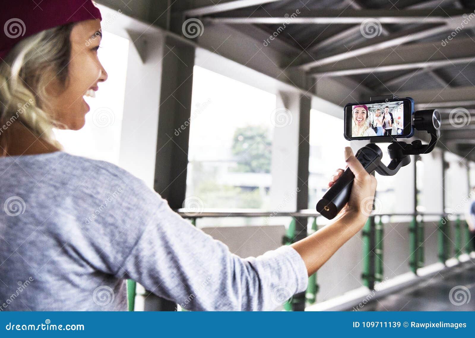 Молодая взрослая женщина путешествуя и vlogging социальная концепция средств массовой информации