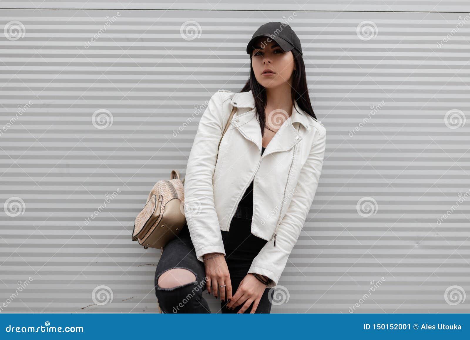 Молодая городская женщина в ультрамодной белой кожаной куртке в винтажных сорванных джинсах в стильной черной бейсбольной кепке