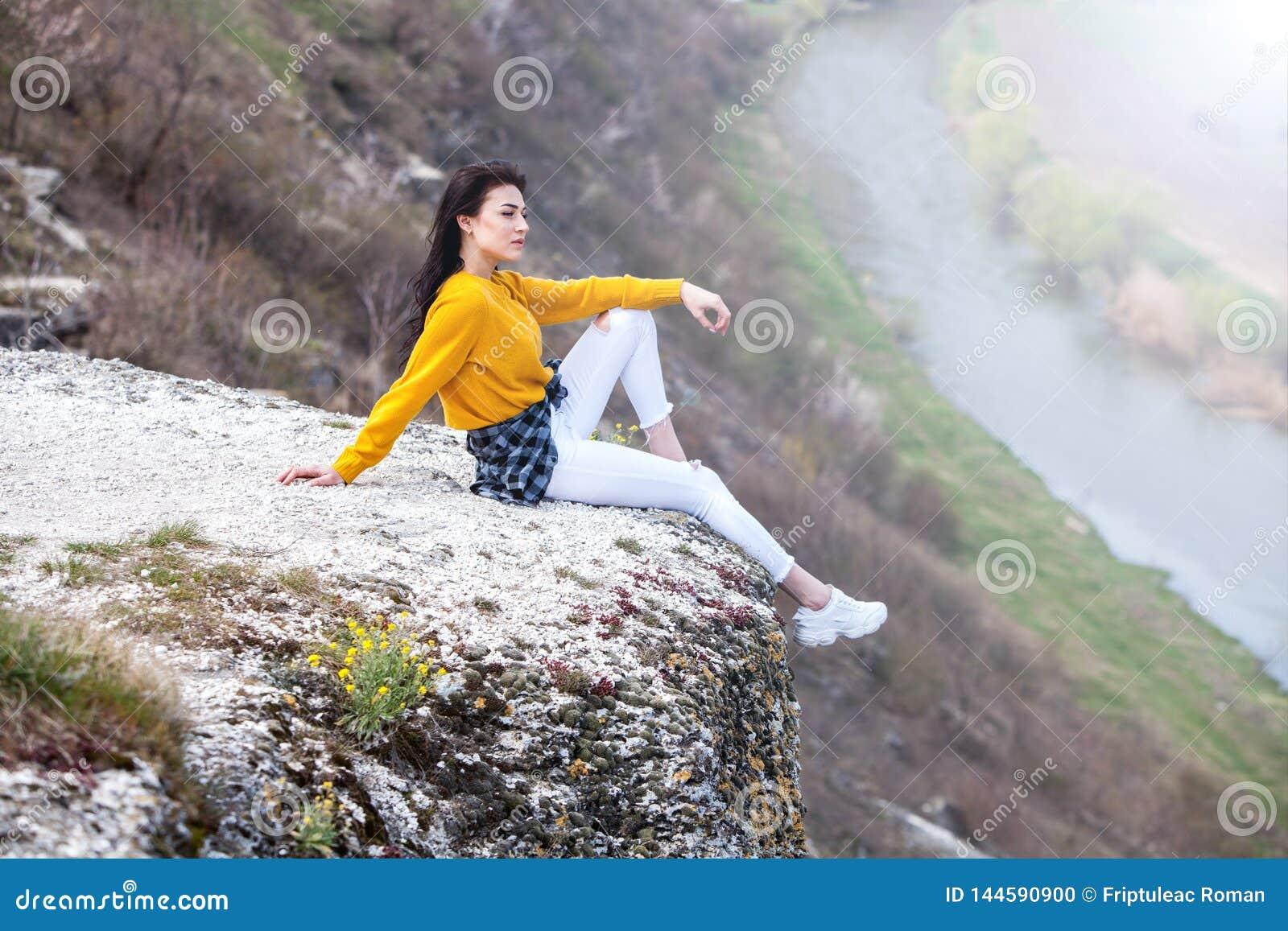 Молодая девушка путешественника сидит на верхней части долины Маленькая девочка любит дикую жизнь, перемещение, свободу Женщина п