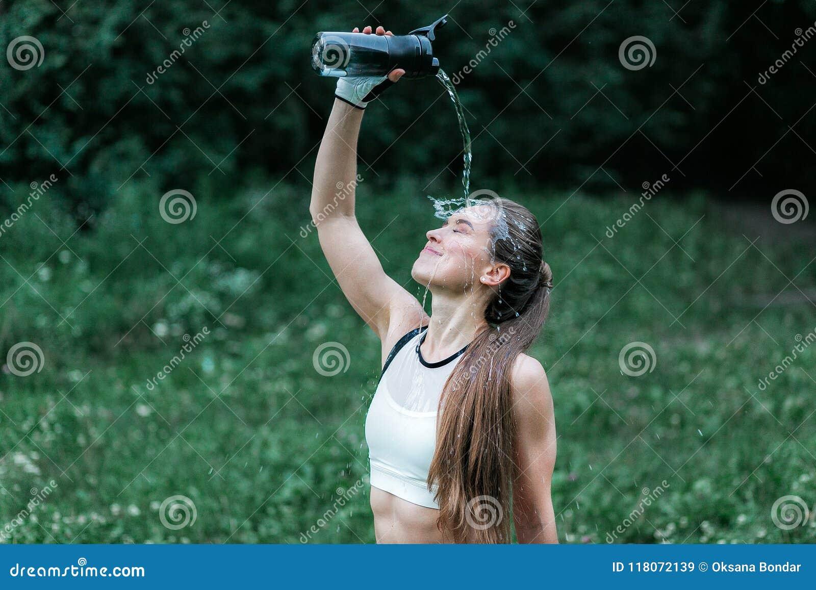 Молодая девушка фитнеса лить холодную воду на стороне после jog, конца вверх по горизонтальной съемке стороны Женщина в лесе прот