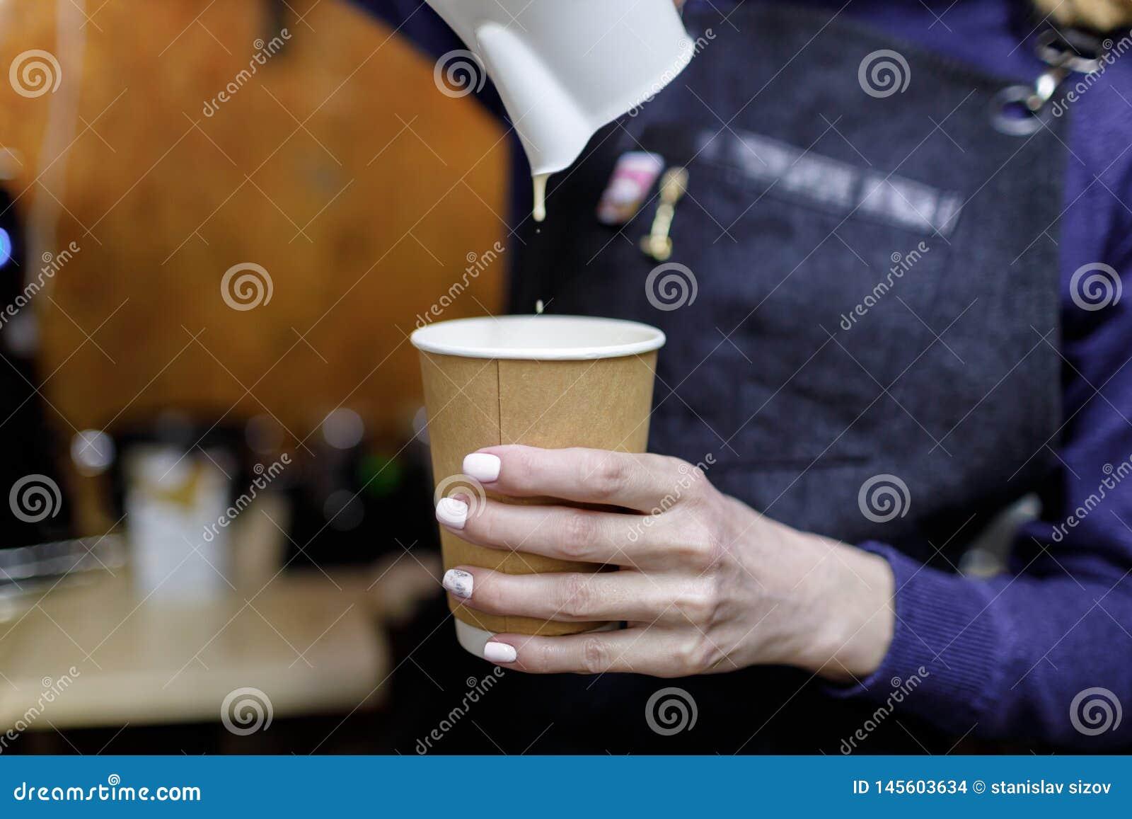 Молодая девушка barista лить стекло капучино