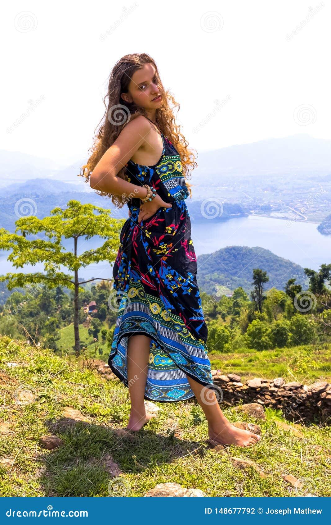 Молодая европейская красивая девушка стоя самостоятельно дикое озеро леса на предпосылке