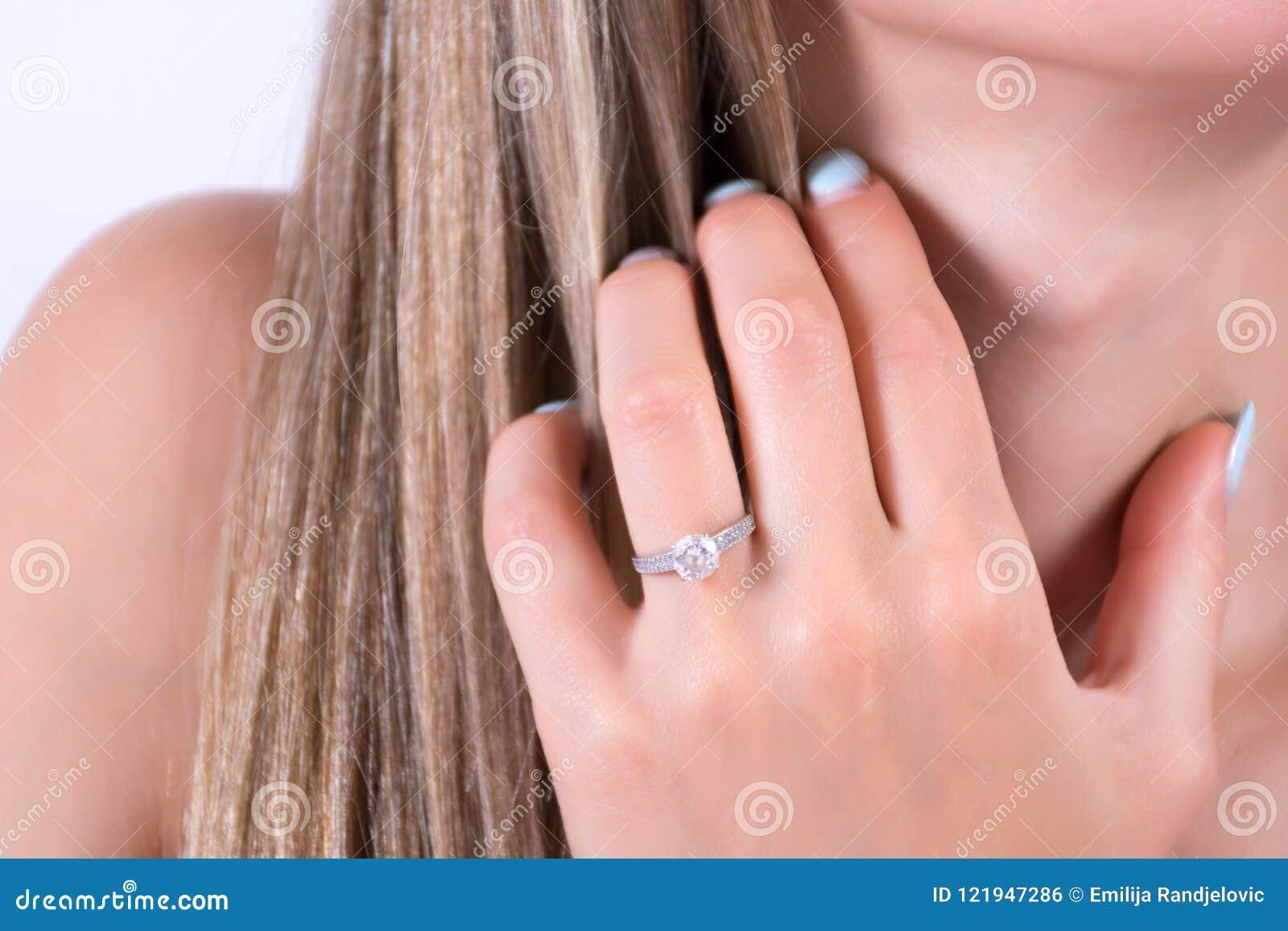 Молодая женская рука с обручальным кольцом захвата на пальце и рука держа в волосах