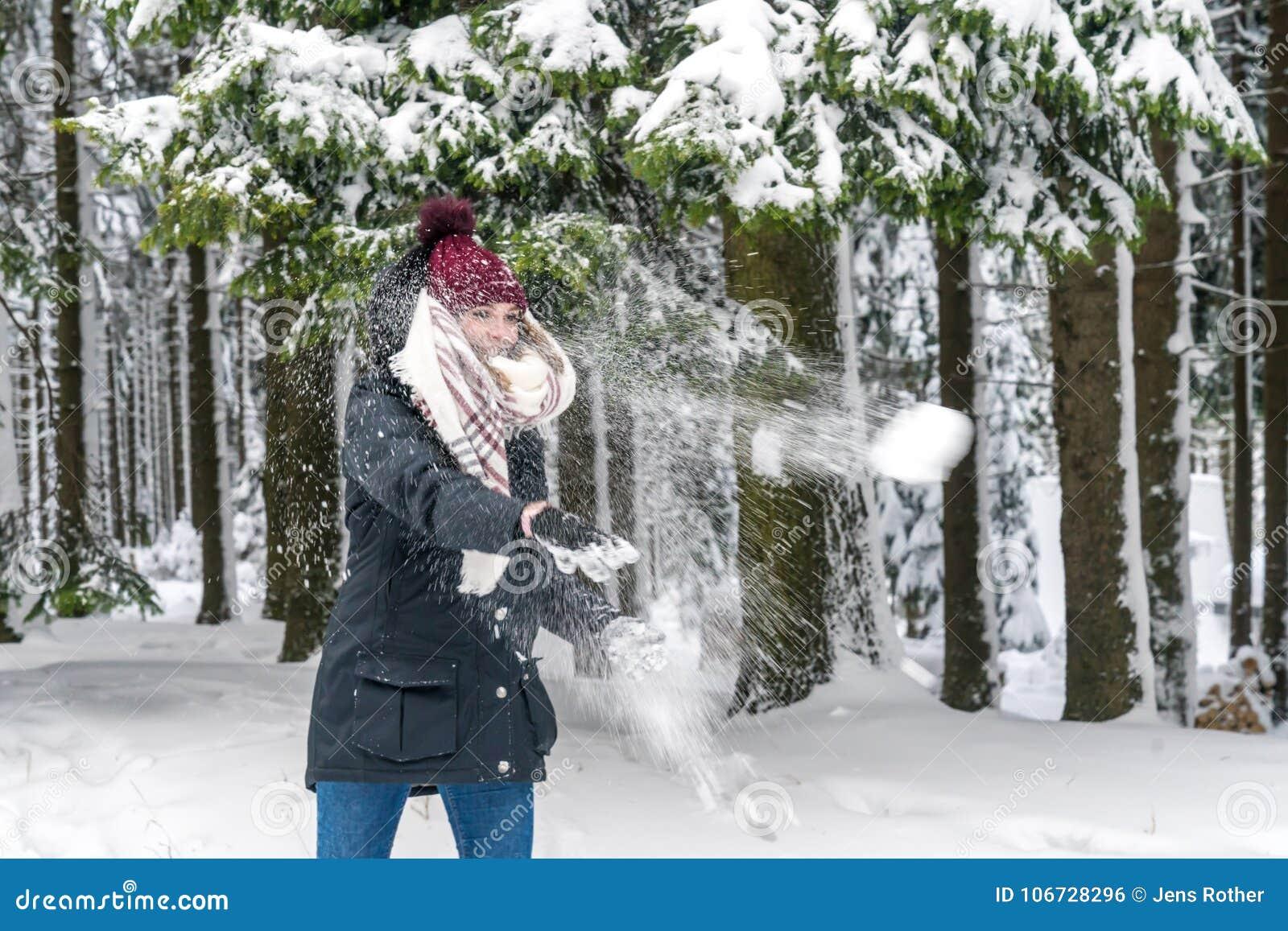 Молодая женщина бросает снежный ком
