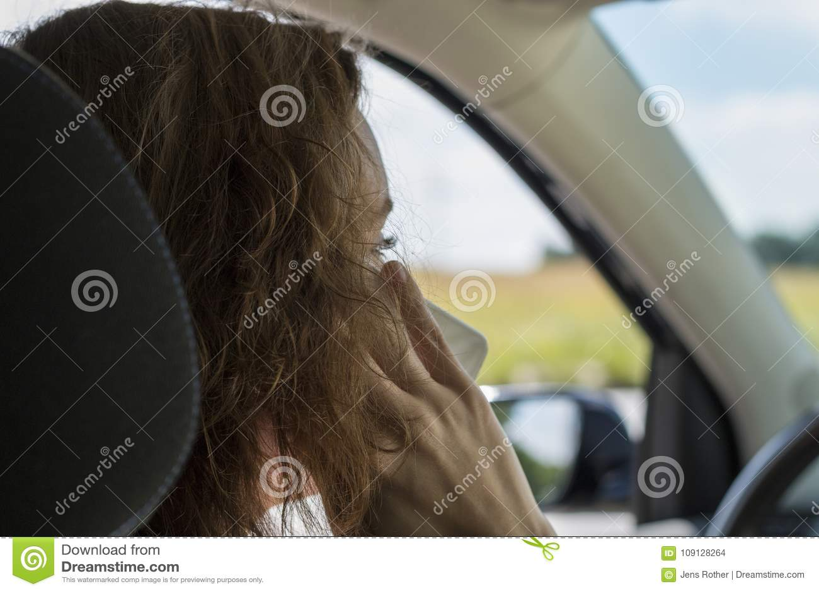 Молодая женщина в автомобиле говорит на телефоне и отвлечена