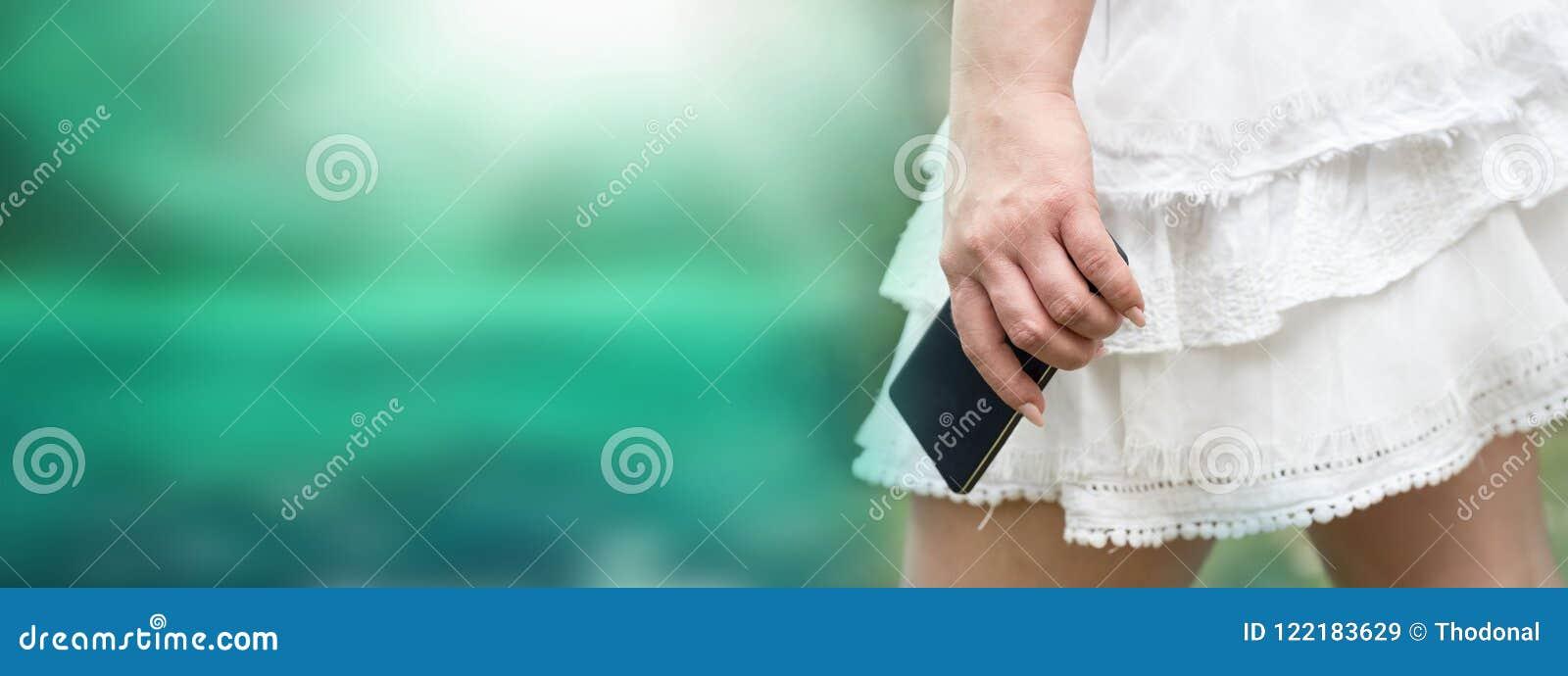 Молодая женщина в белой юбке с мобильным телефоном в ее руке