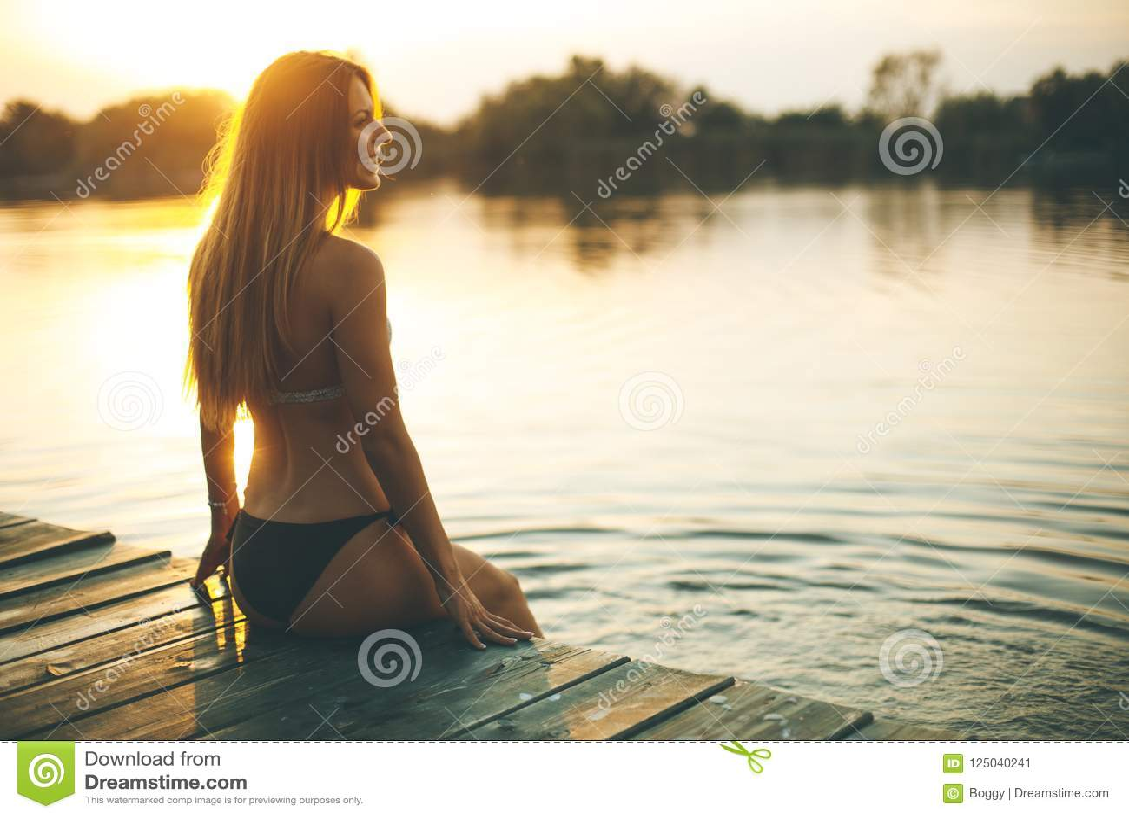 Молодая женщина в бикини на пристани рекой