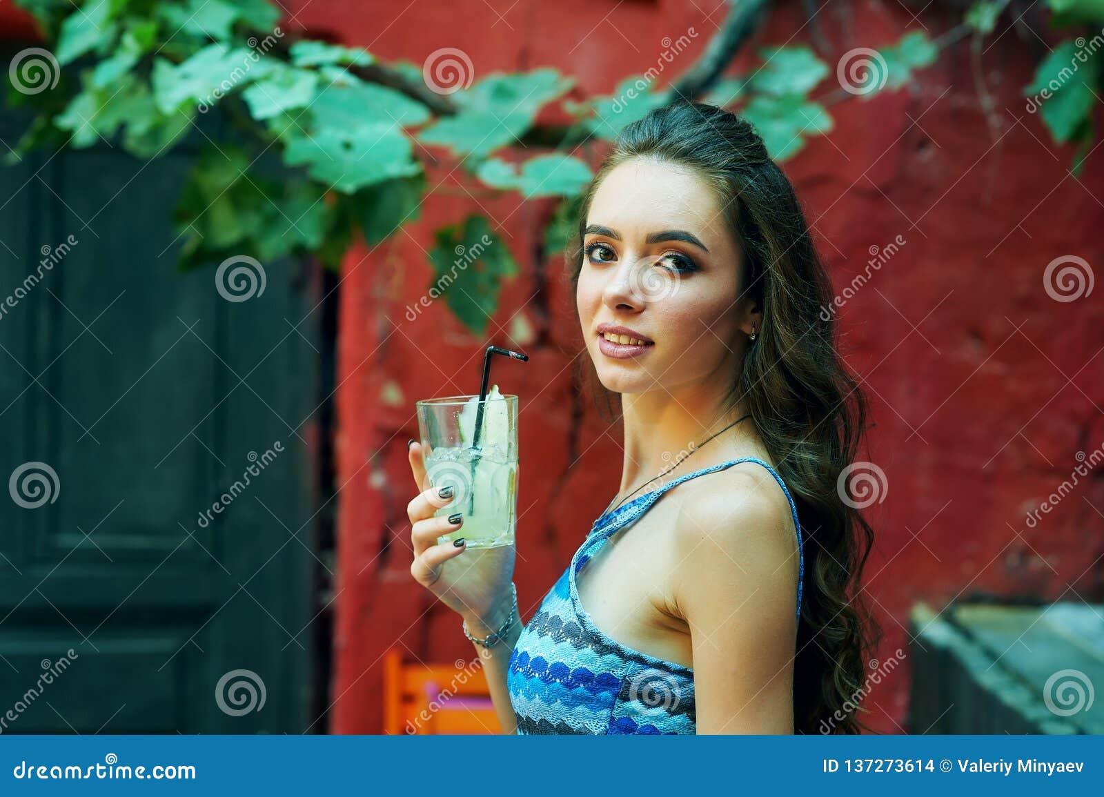 Молодая женщина в кафе улицы со стеклом освежающего напитка