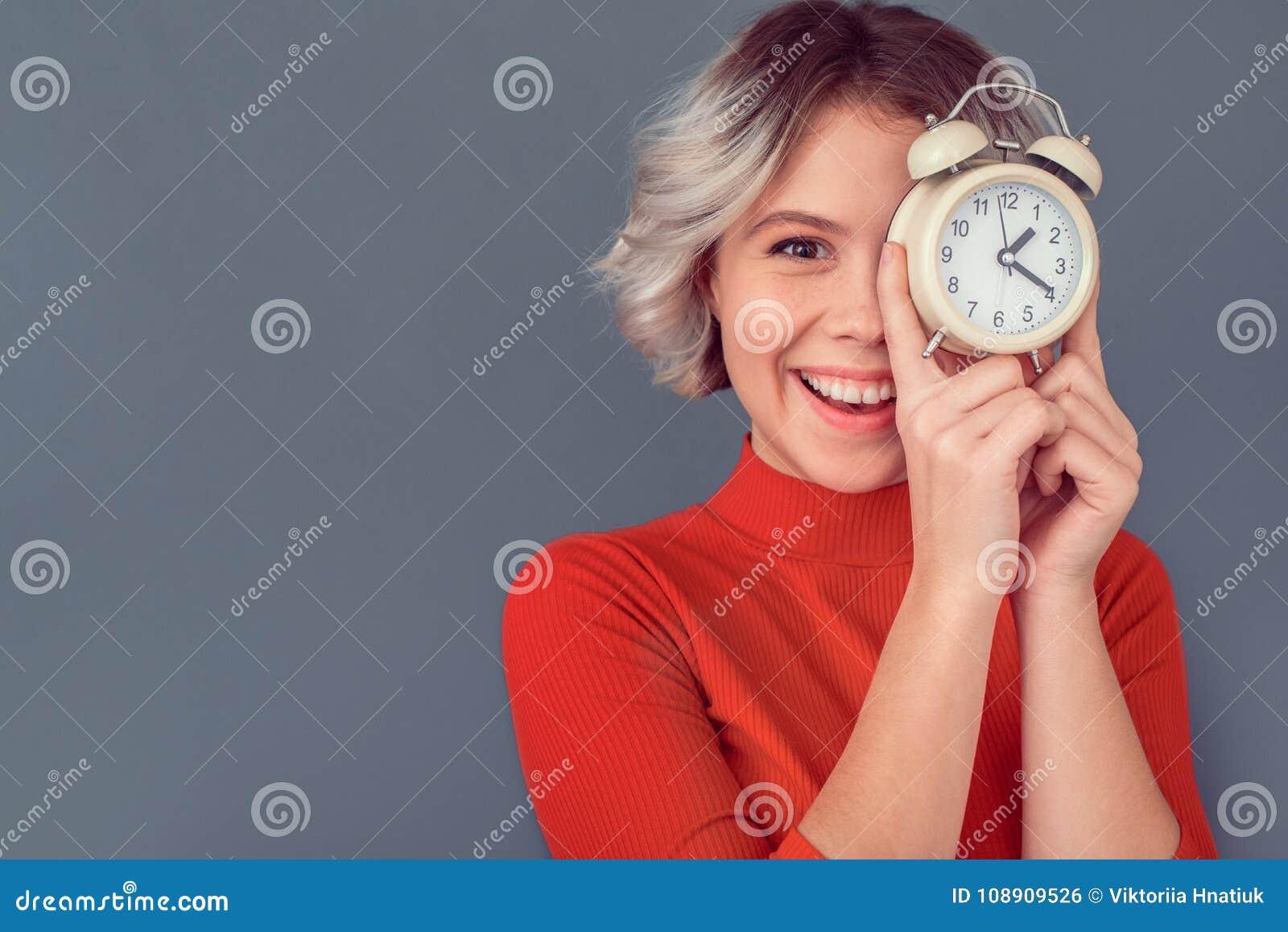 Молодая женщина в красной блузке изолированной на сером контроле времени стены