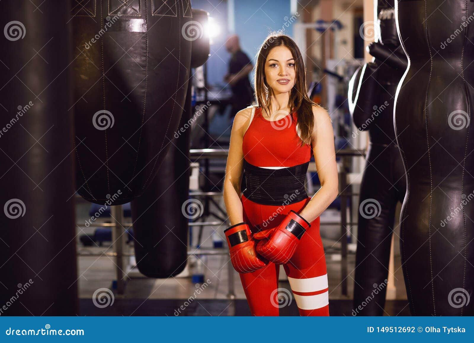 Молодая женщина в красных одеждах спорт и кладя в коробку перчатках, поездах с кладя в коробку грушей в темном спортзале