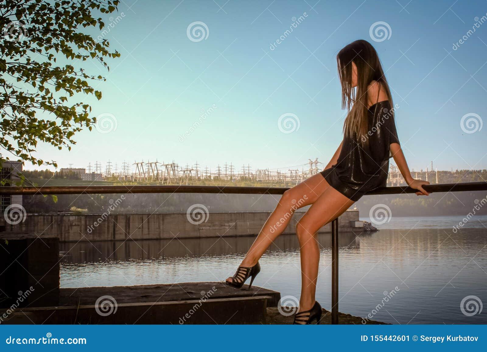Молодая женщина в милом платье лета сидя на пристани смотря заход солнца