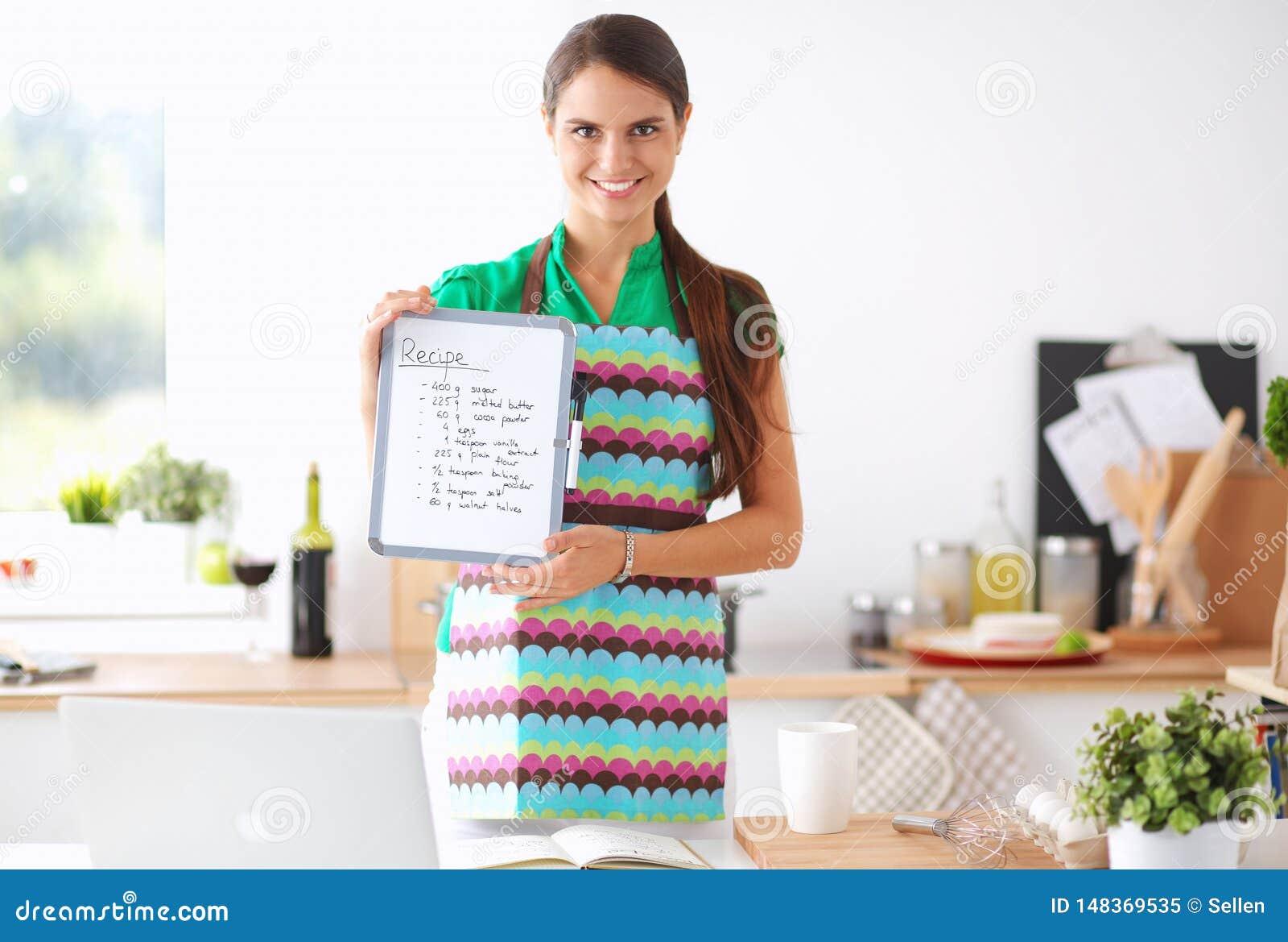Молодая женщина в рисберме варит в кухне