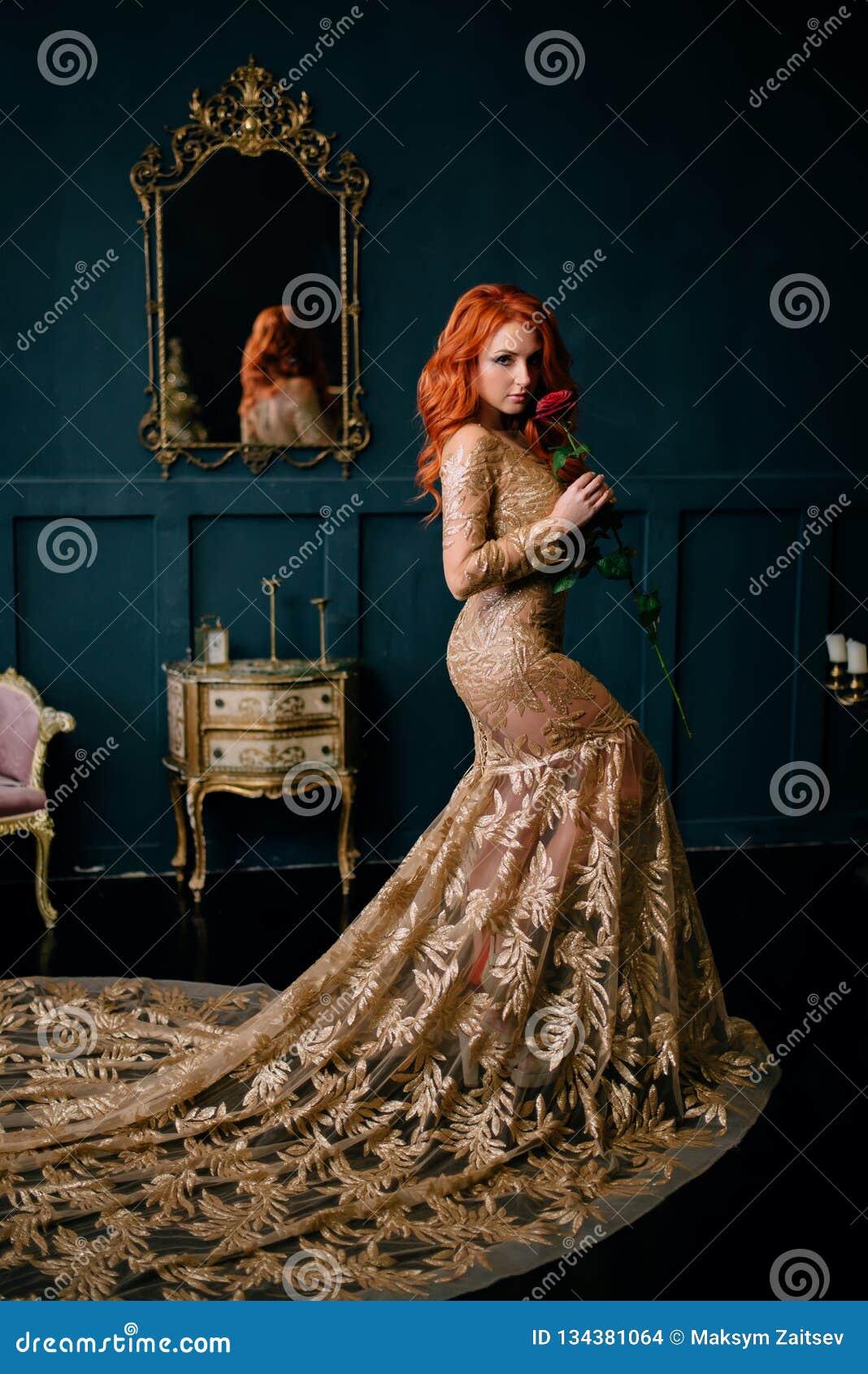 Молодая женщина в роскошном положении платья в винтажном интерьере