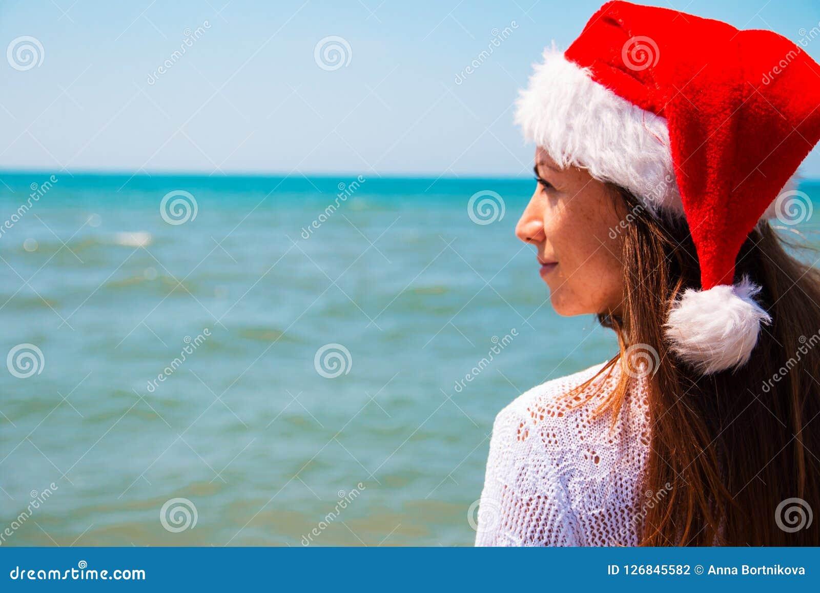 Молодая женщина в шляпе santa на тропическом пляже рождество соединило пустое специально изображение офиса компьтер-книжки интерн