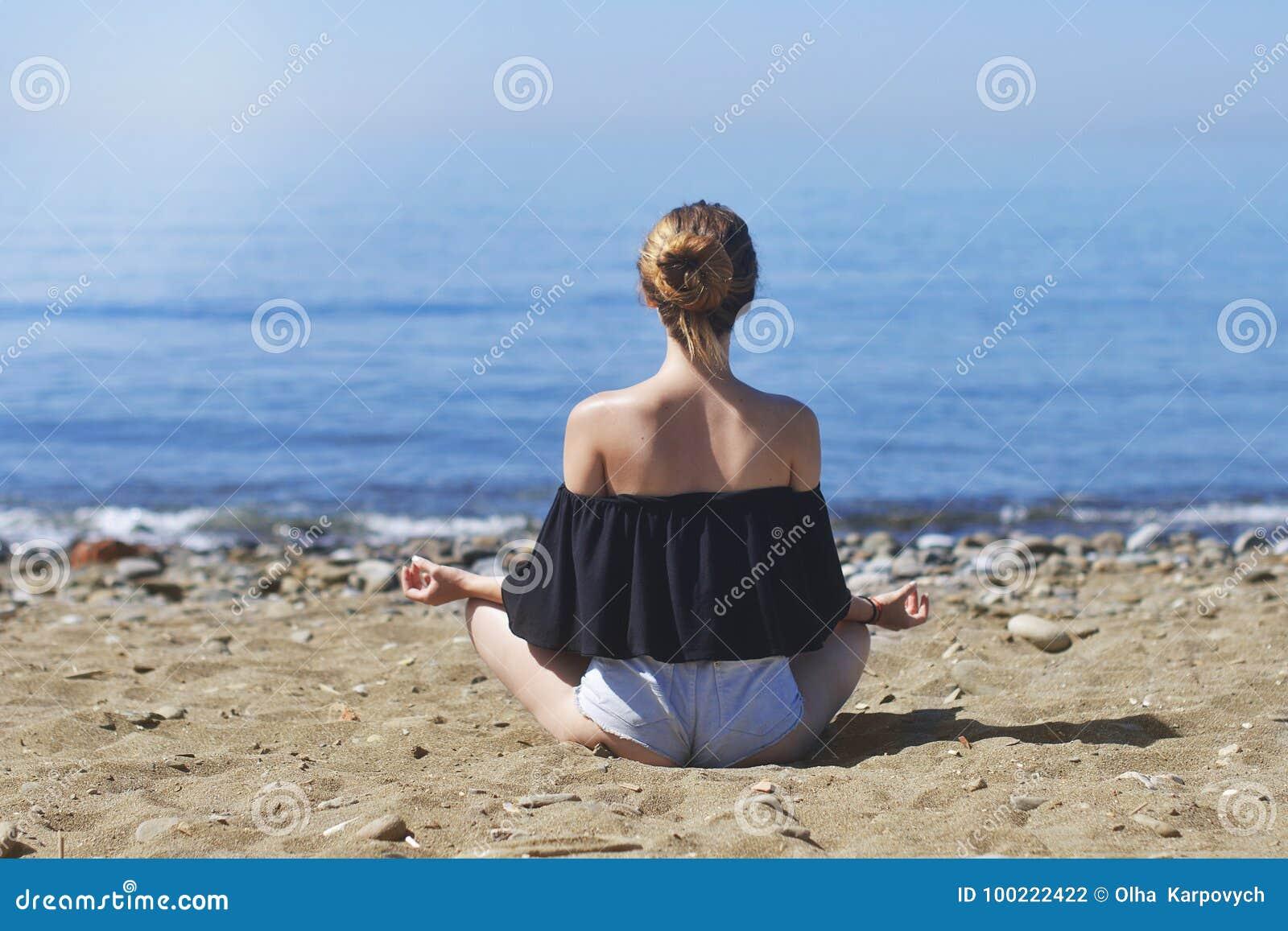 Молодая женщина делает раздумье в представлении лотоса на море/пляже, сработанности и созерцании океана Йога красивой девушки пра