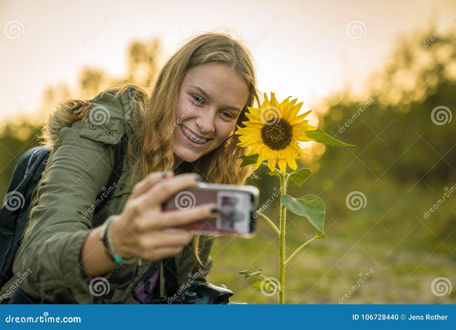 Молодая женщина делает selfie с солнцецветом