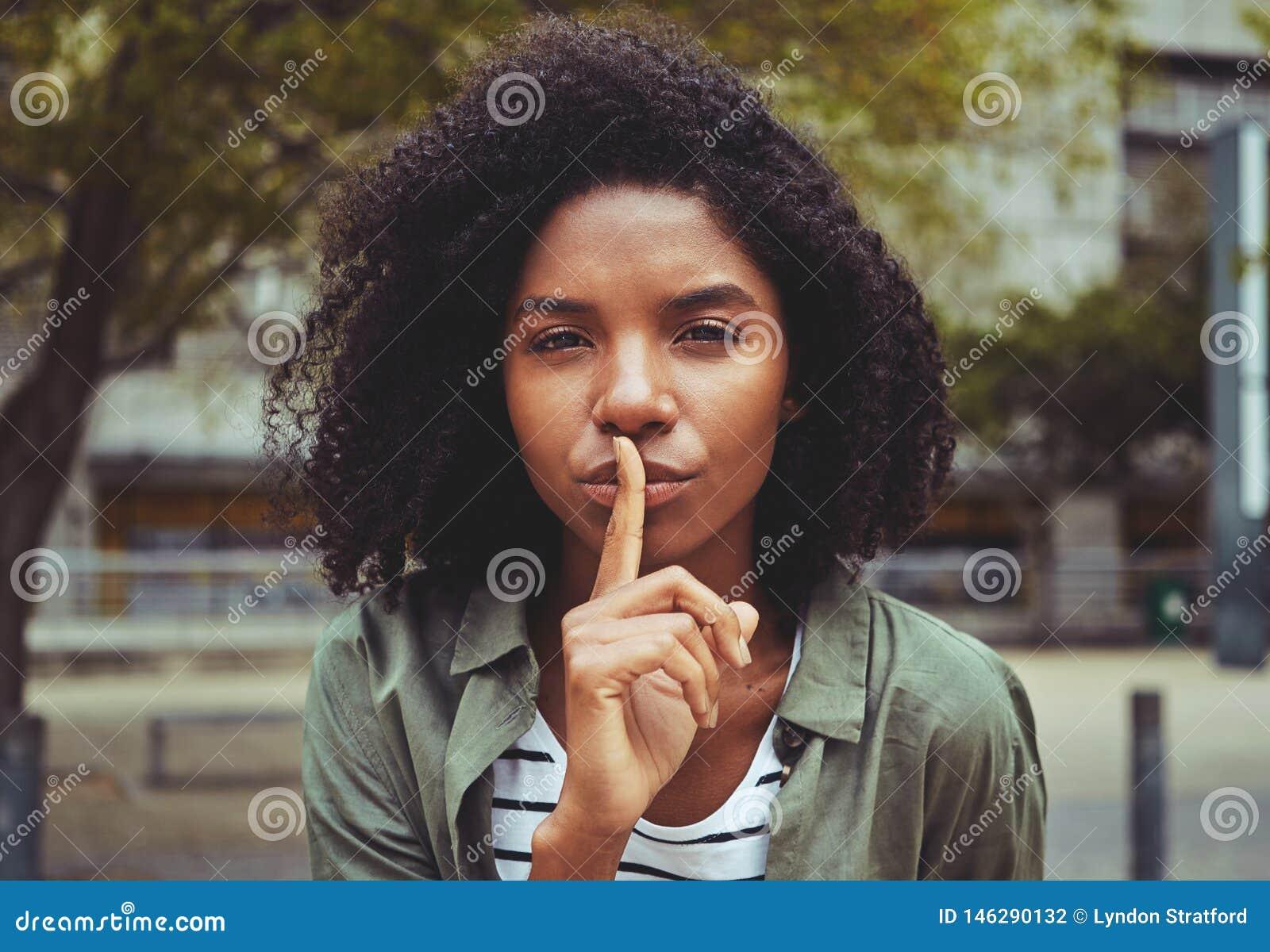 Молодая женщина делая для того чтобы заставить замолчать жест