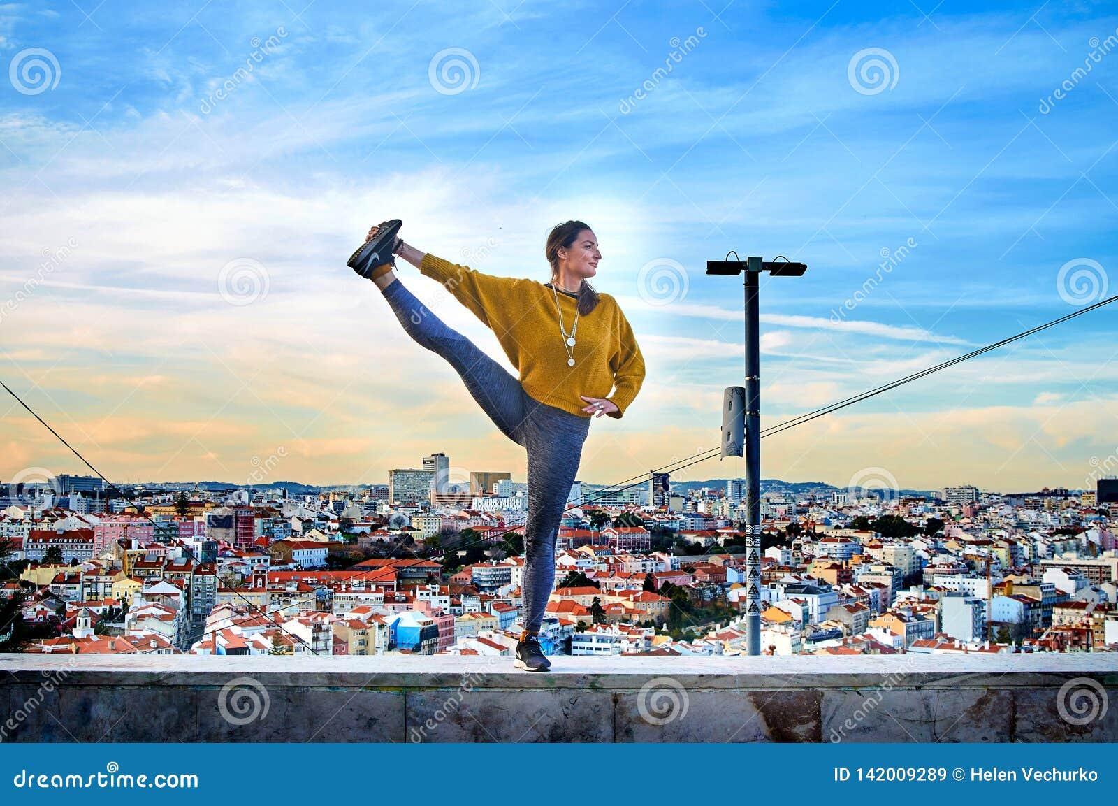 Молодая женщина делая тренировку йоги outdoors на предпосылке вида на город Лиссабона